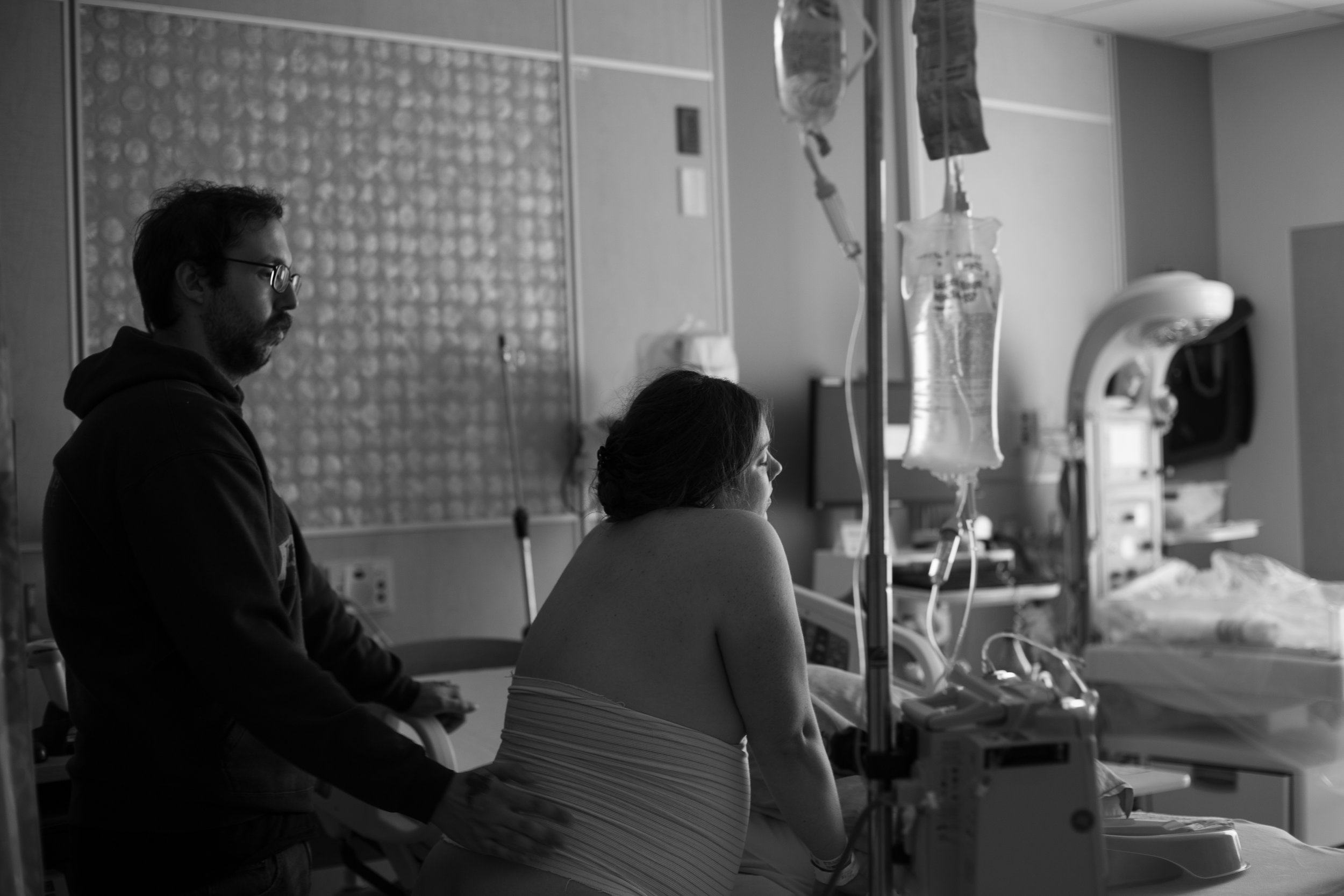 Black and white image of a man giving counter pressure to a woman in the hospital.