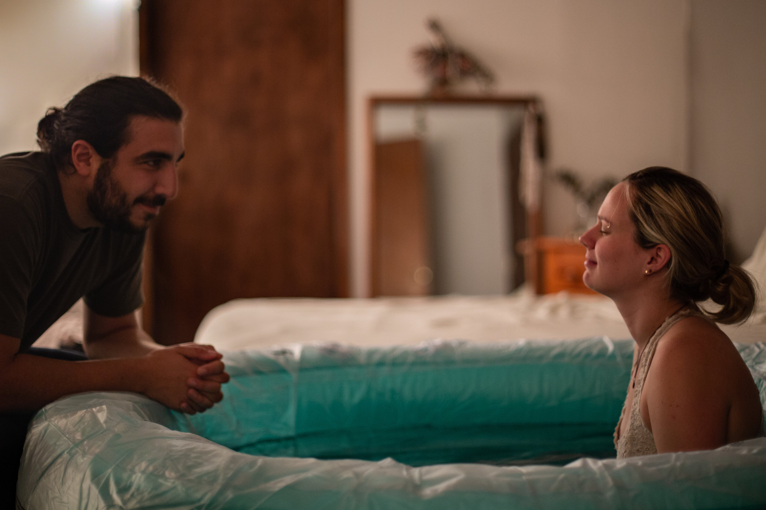 A woman in a birth tub smiles as her husband says something sweet to her.
