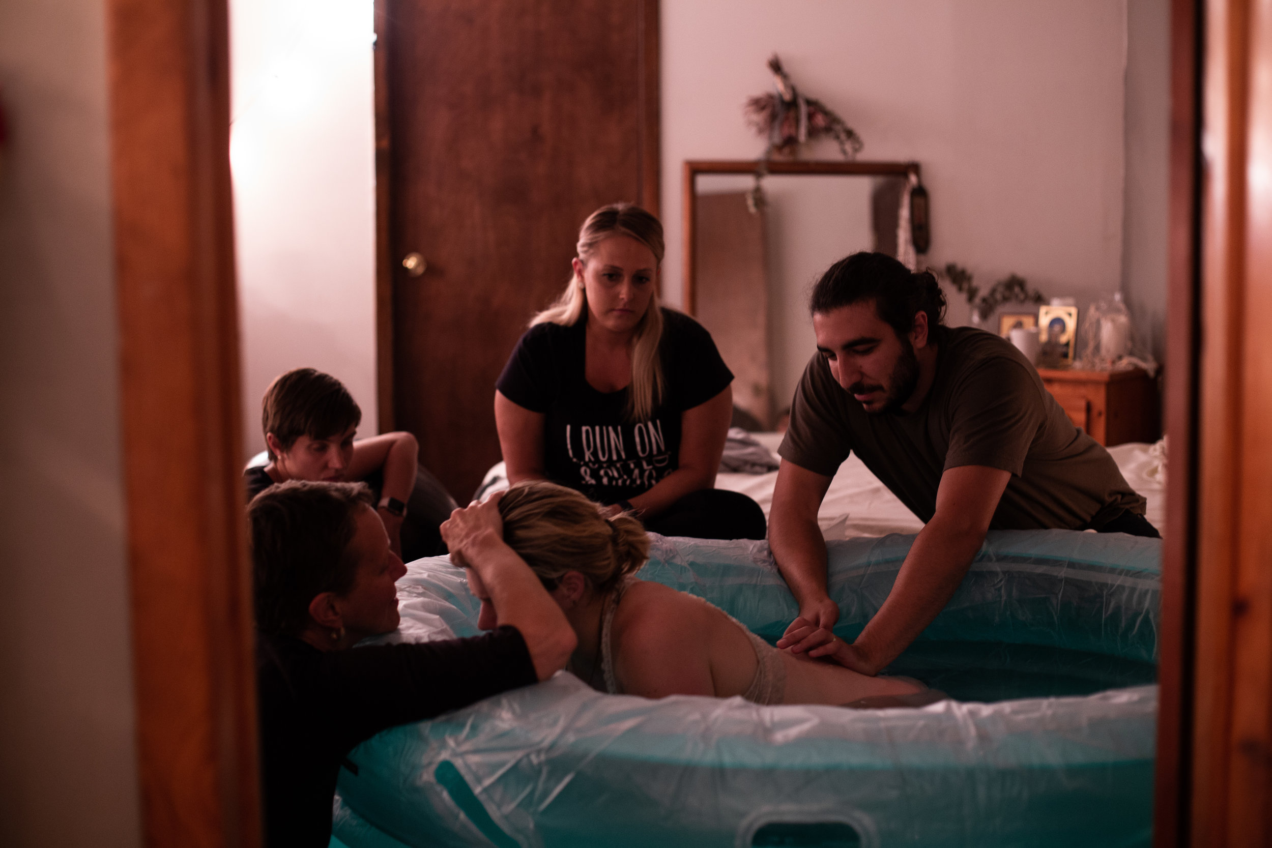 A woman in a birth pool surrounded by supportive people