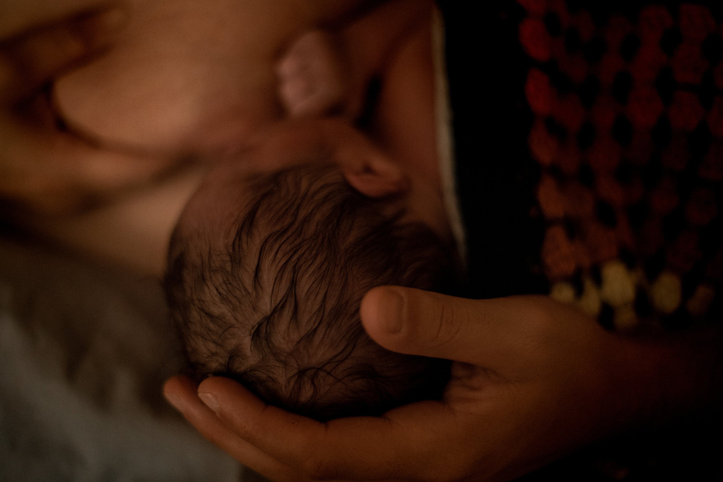 A newborn's head cupped gently by her father.