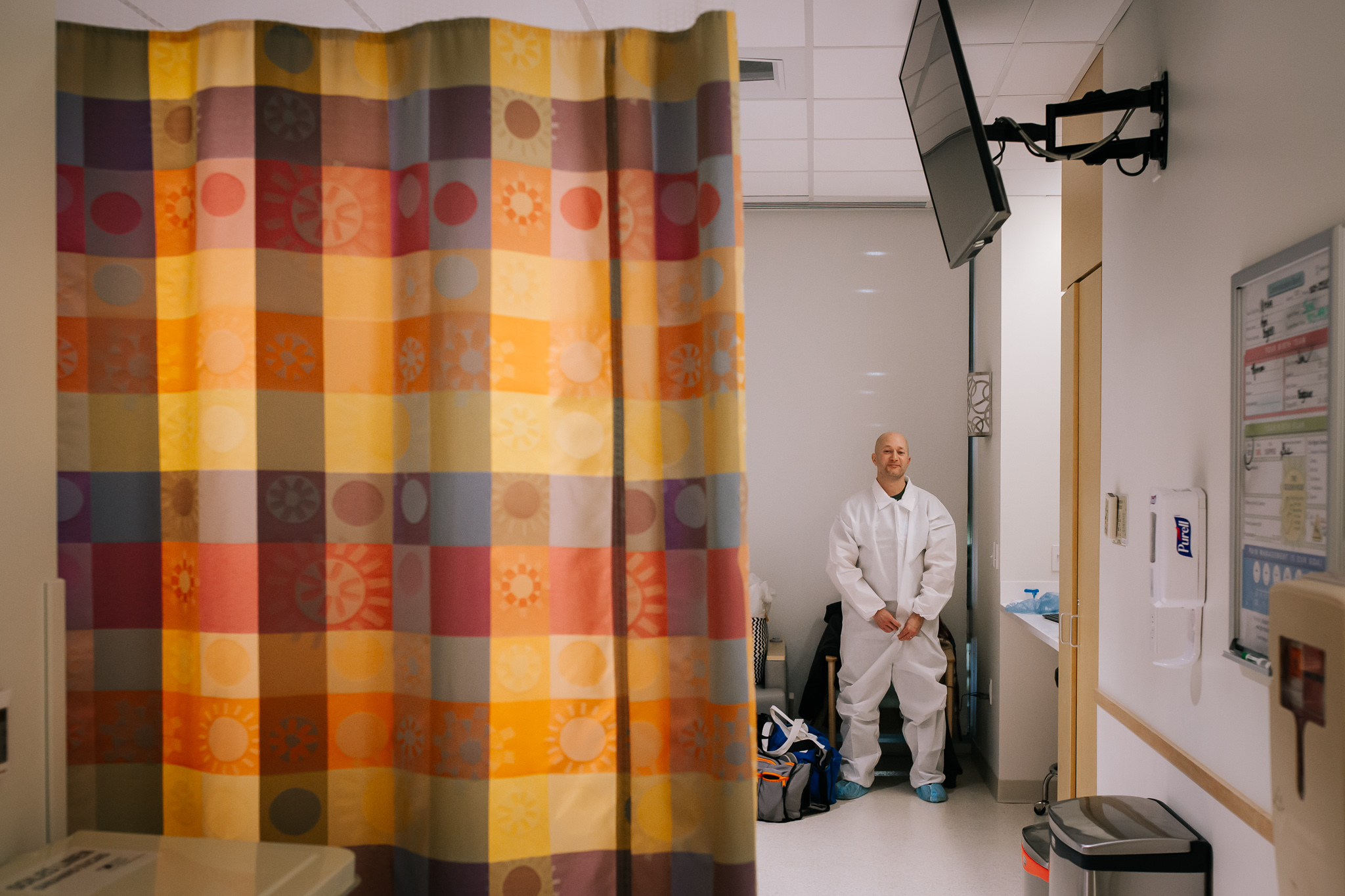 Man behind a hospital curtain gets a sterile suit on before a cesarean section.