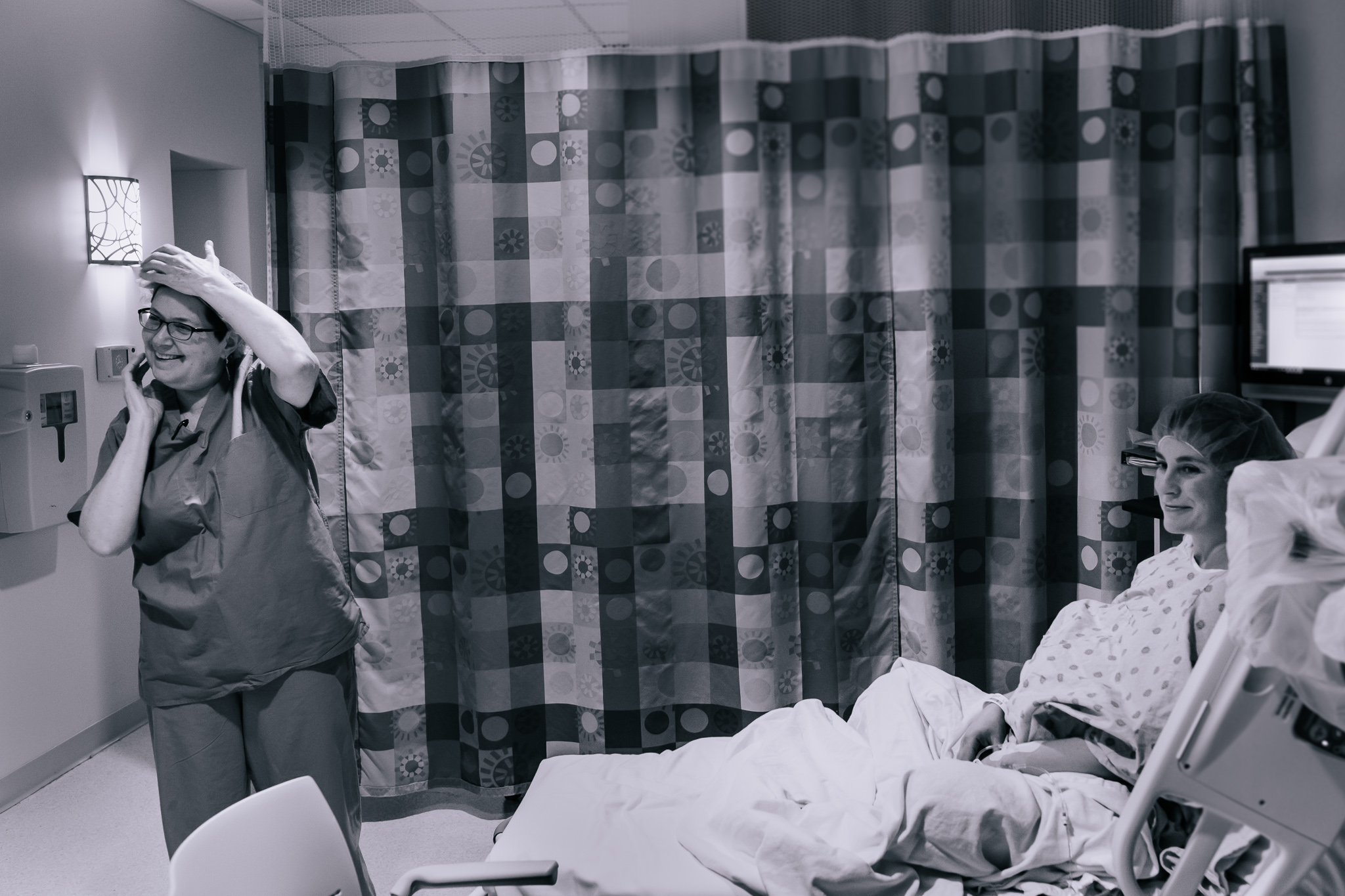 A black and white image of an OBGYN and a pregnant woman before a c-section.
