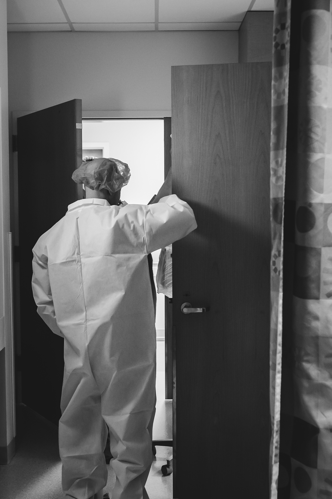 A man in surgery scrubs walks out of a hospital room.