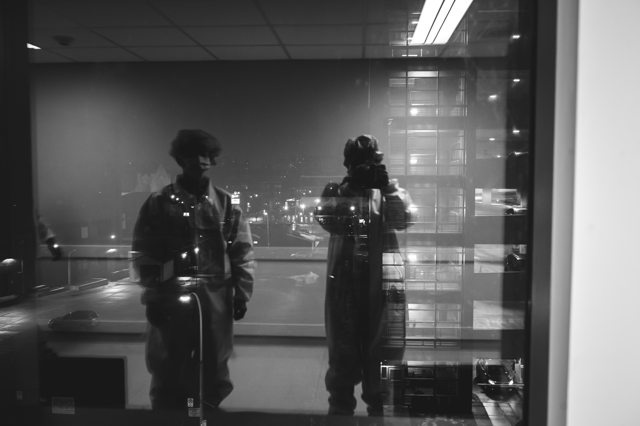 Black and white reflection of a man and photographer in a hospital window.