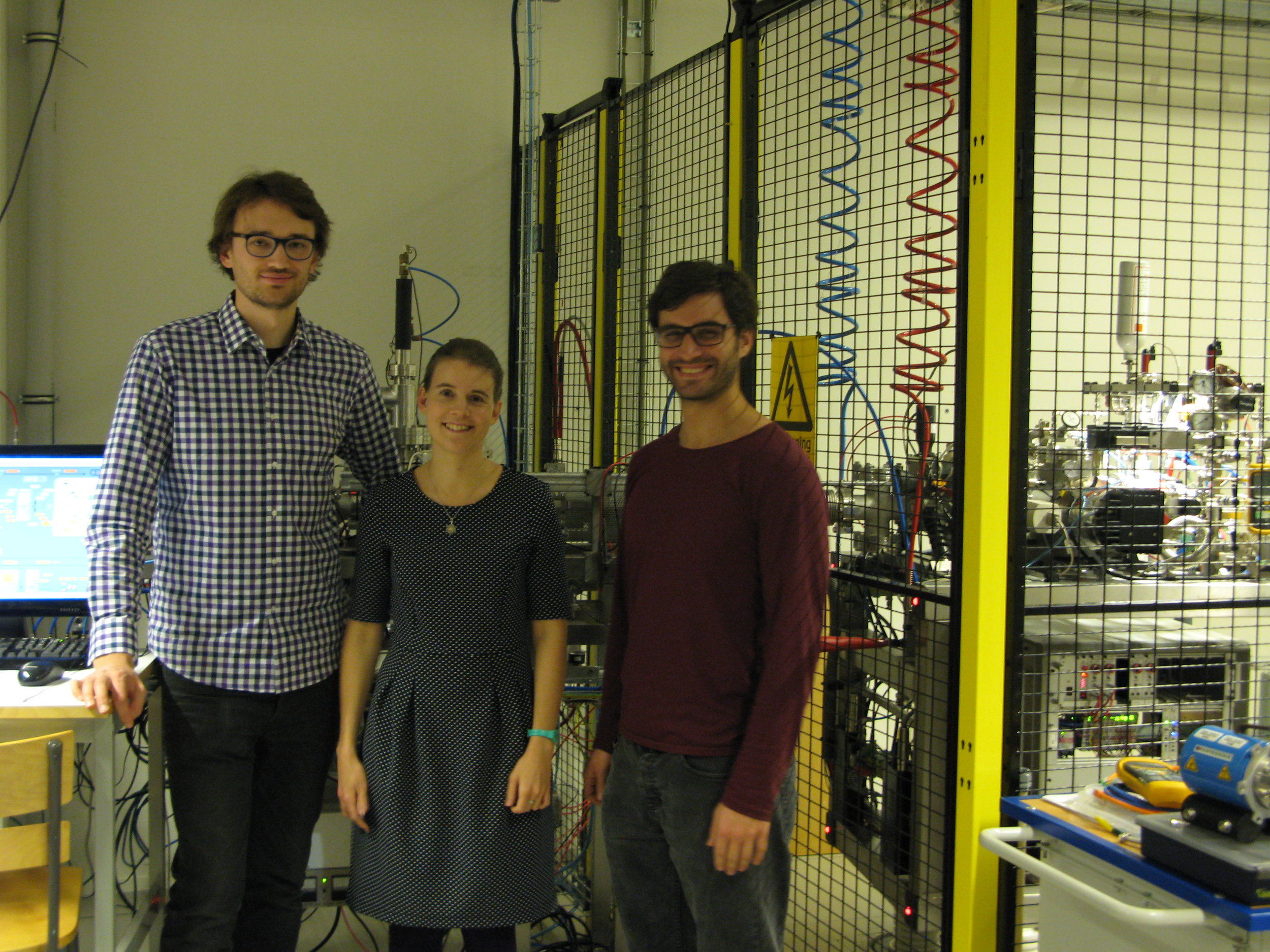 Michael Gatchell, Linnea Lundberg, and Simon Albertini in front of the high-energy ion source platform used to produce C60+ for their experiments.