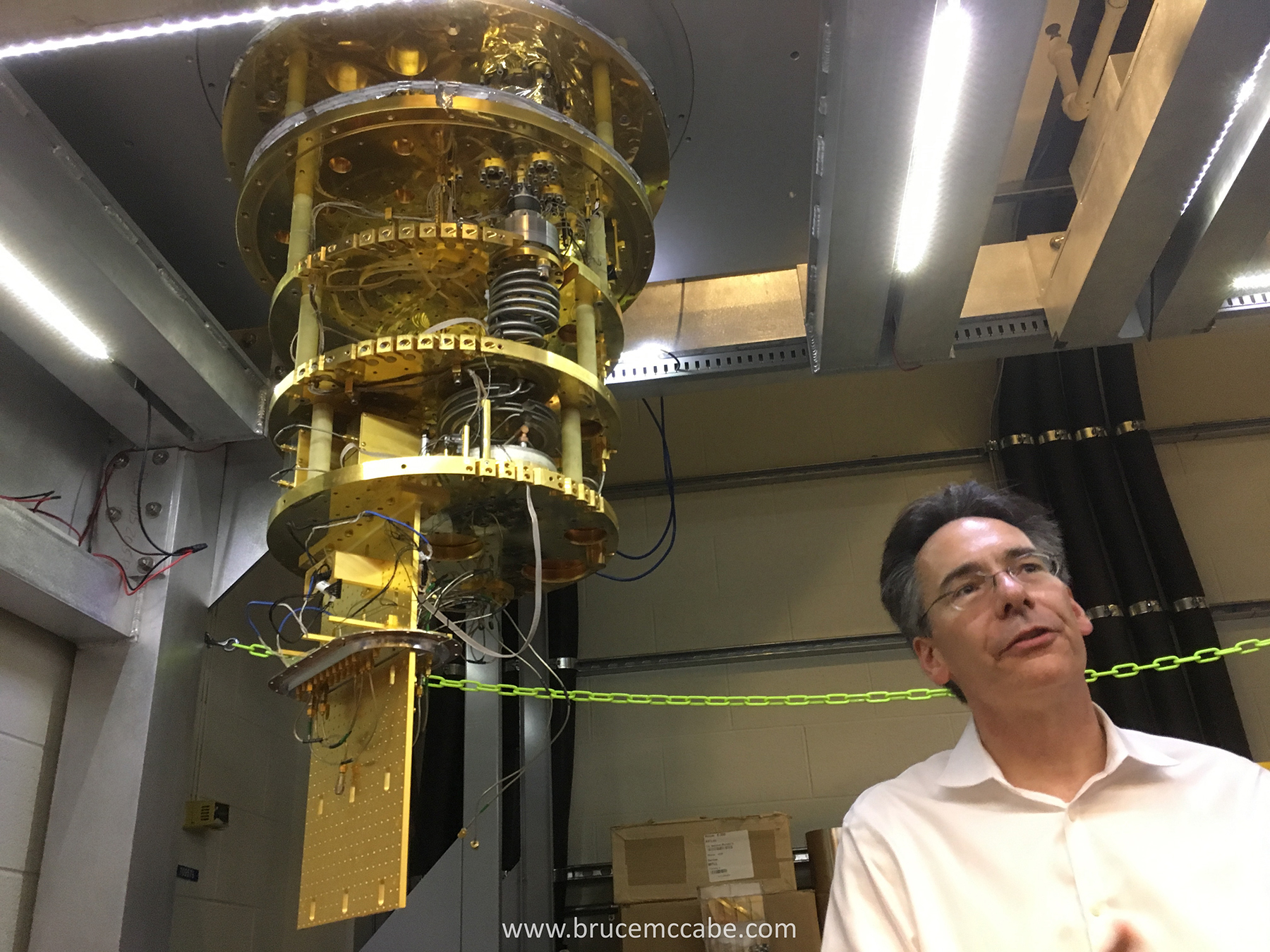 Prof William Oliver showing quantum hardware at MIT Lincoln Lab.jpg