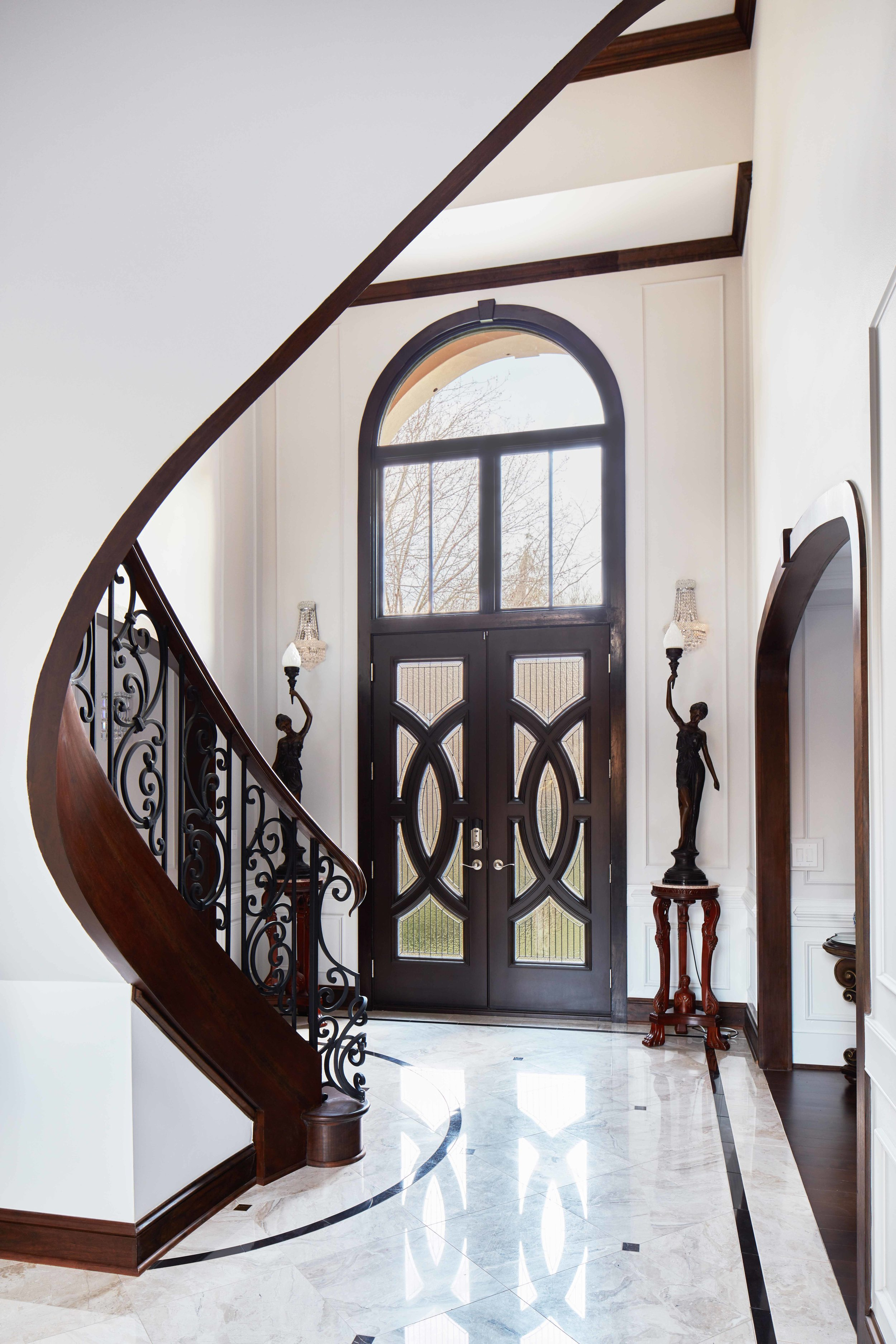 Finished Staircase: The curved staircase becomes a sculptural element that frames the front entry from the Great Room.