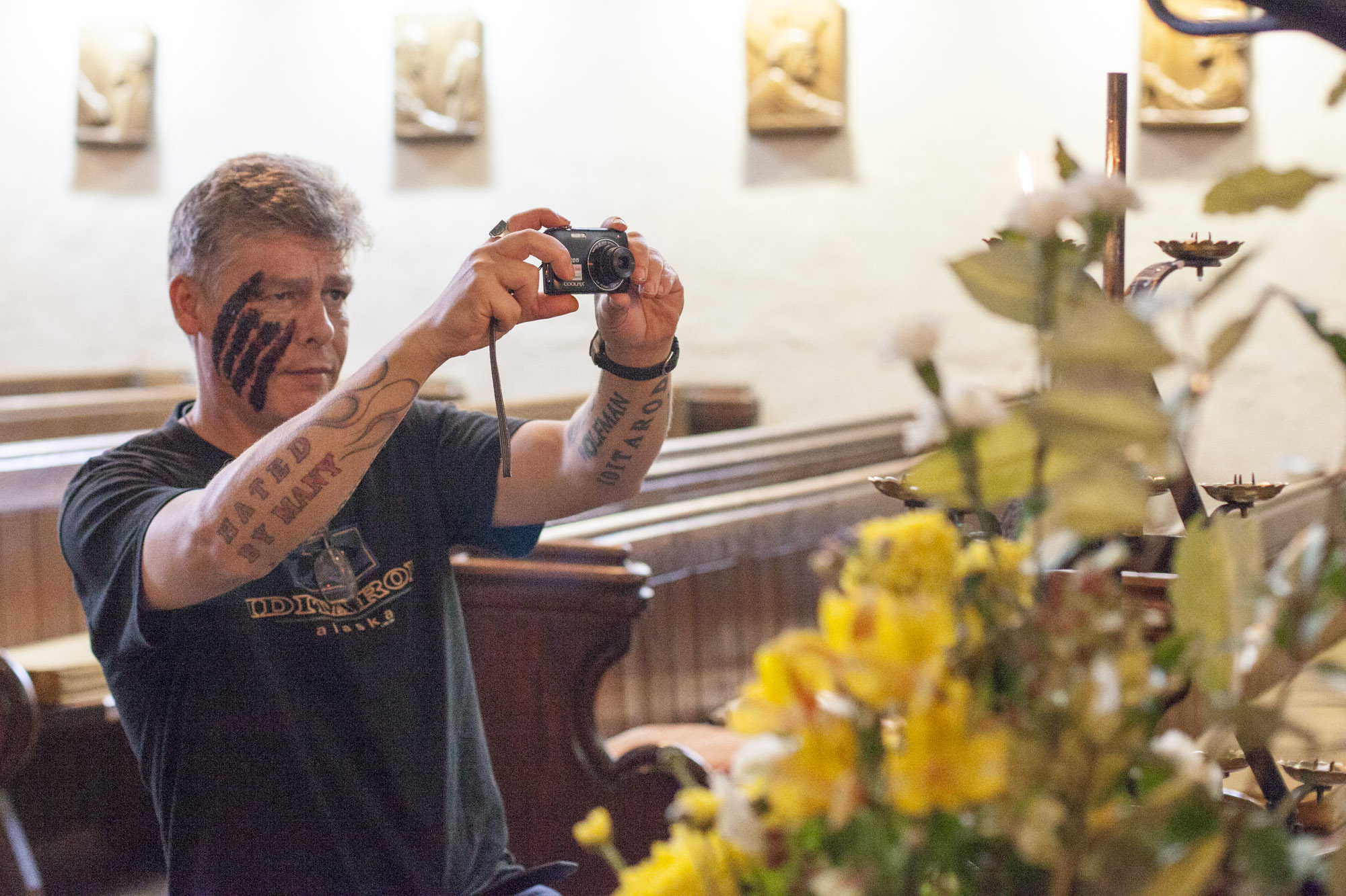 Man taking photo of flowers during a mindfulness photography workshop for staff at Crisis Oxford