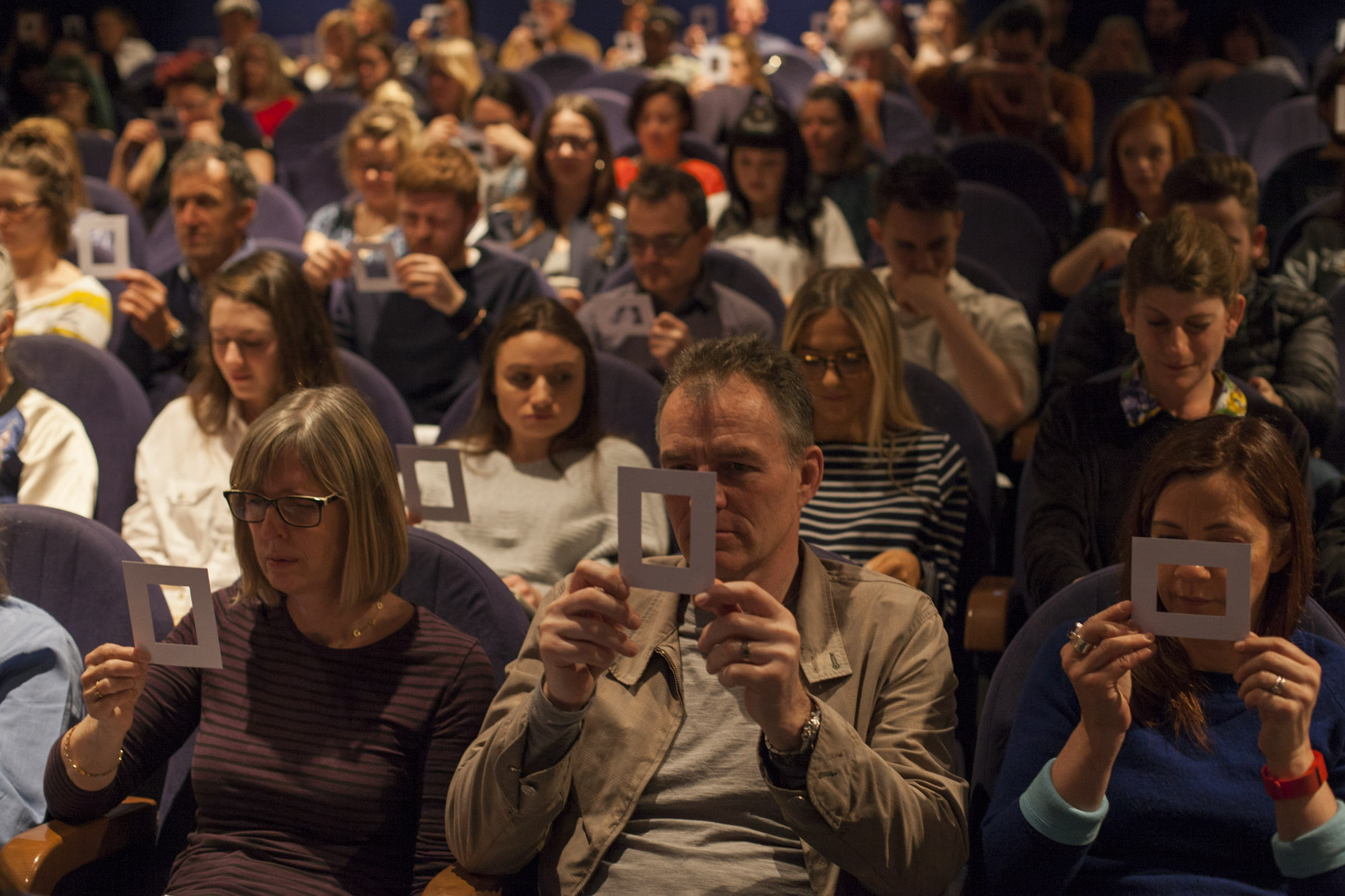 room of people holding up photo mounts during mindfulness photography talk by ruth davey professional photographer gloucestershire