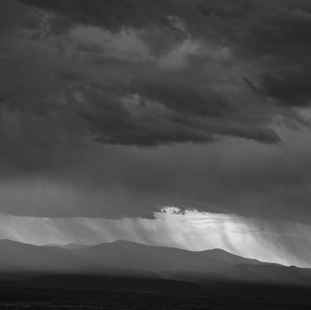 Watching the summer storm over Los Alamos 40 miles away from the porch at Cerro Pinon.  #newmexico #newmexicotrue #santafe #reinhardziegler #storm #losalamosnm #newmexicolife #bnw #bnwphotography #bnw_drama