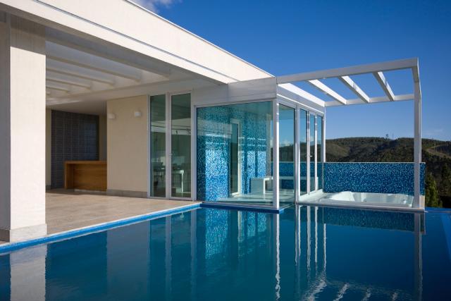 Divisória em laminado temperado para área de sauna com acesso à piscina