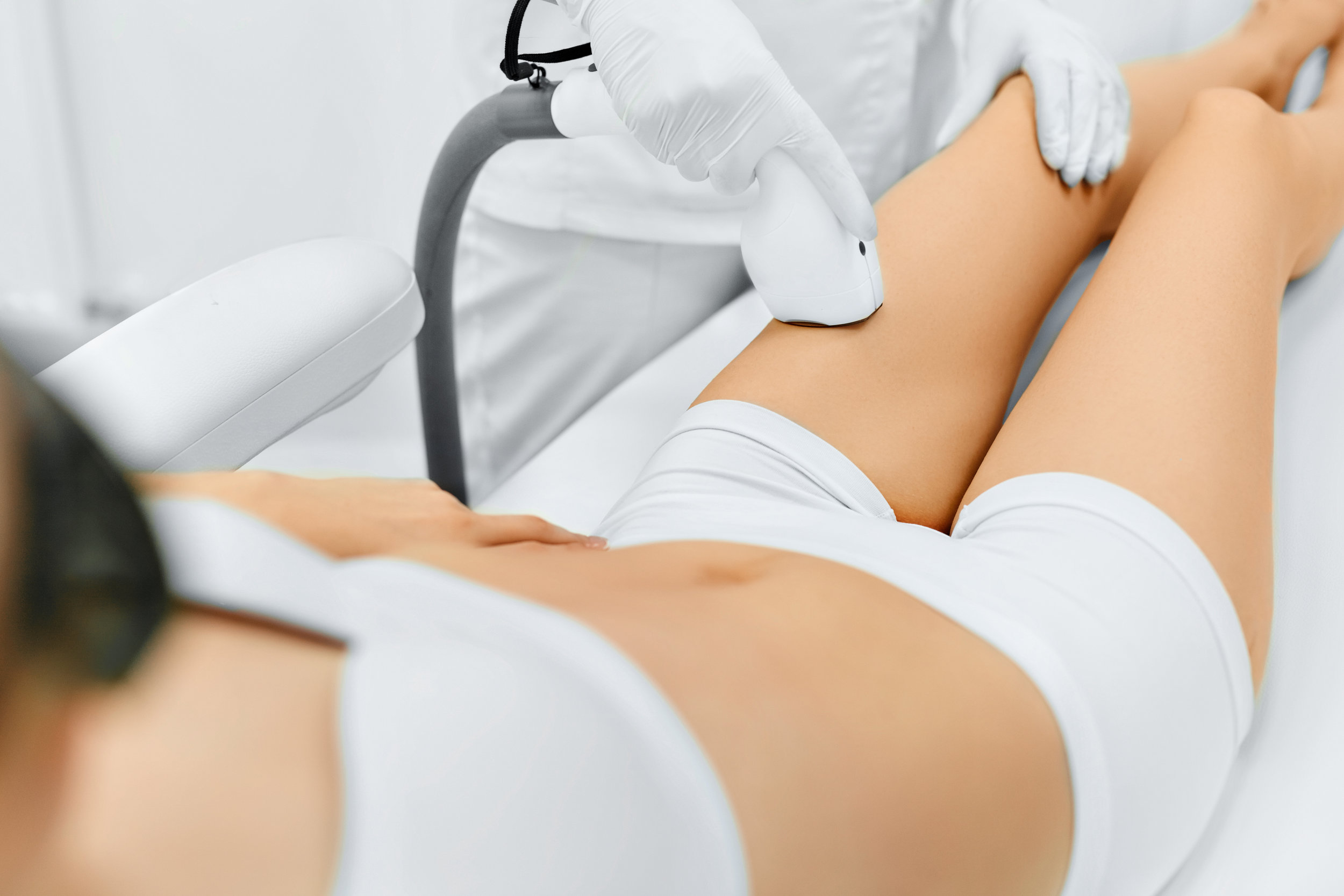 Woman Undergoing Hair Removal Treatment On Her Legs
