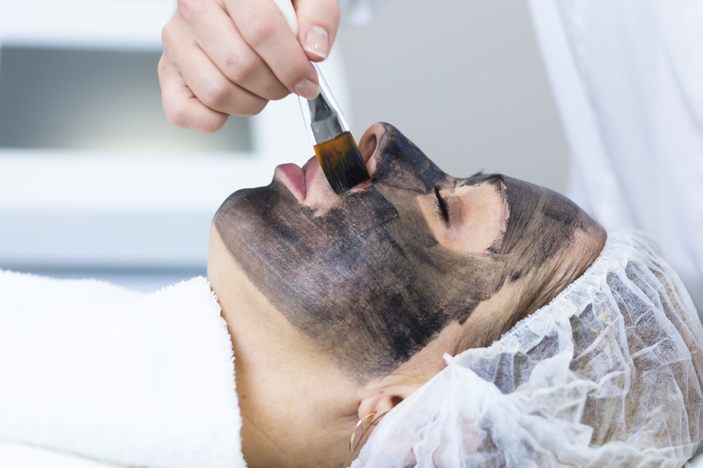Preparing a female client for a carbon laser facial.