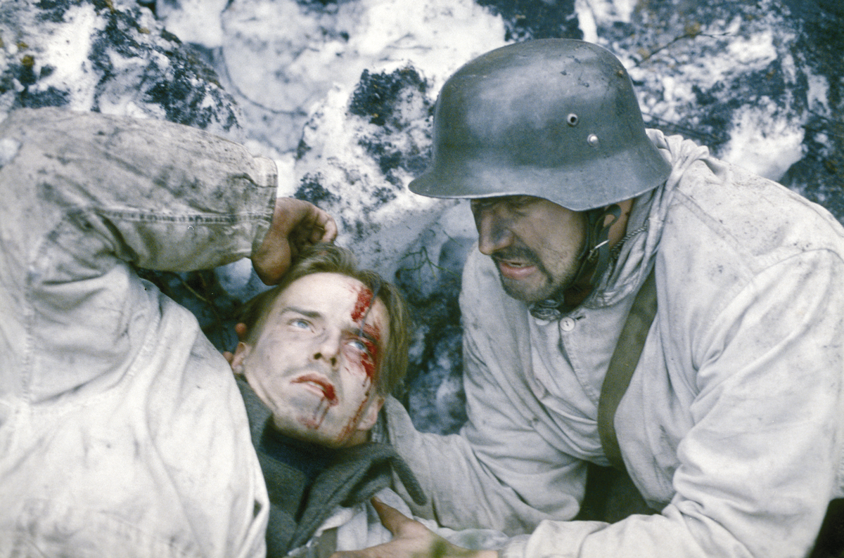 Martti and a wounded Paavo (Konsta Mäkelä) shelter in a trench