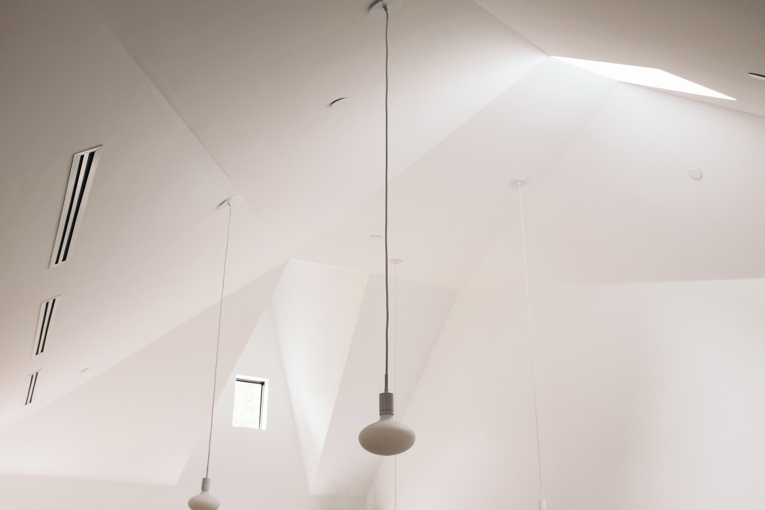 Sculpted ceiling with angular geometry, skylight, and pendant lights