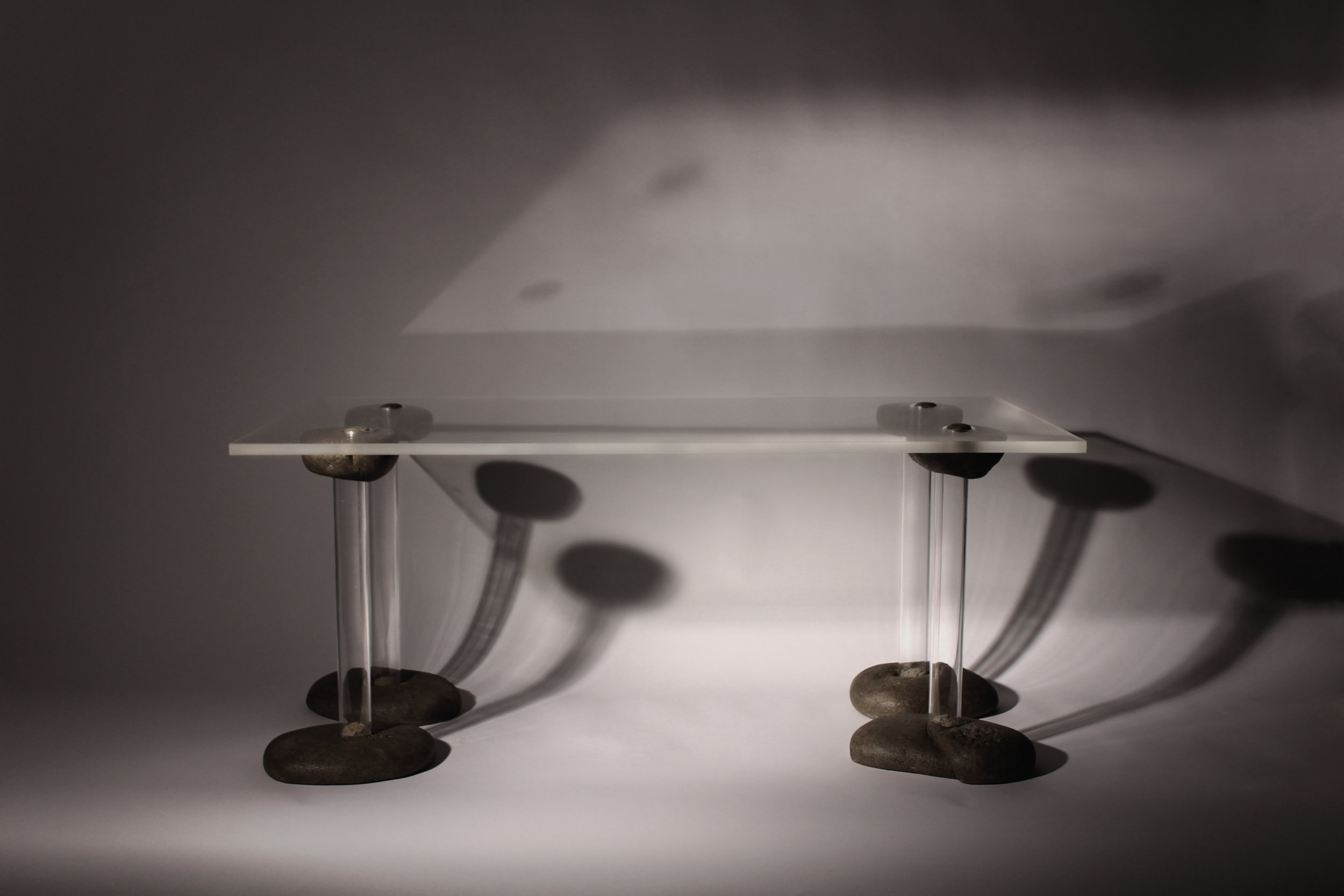 The plexiglass tabletop is held to the legs with fabric-formed joint pieces which create a removable form joint
