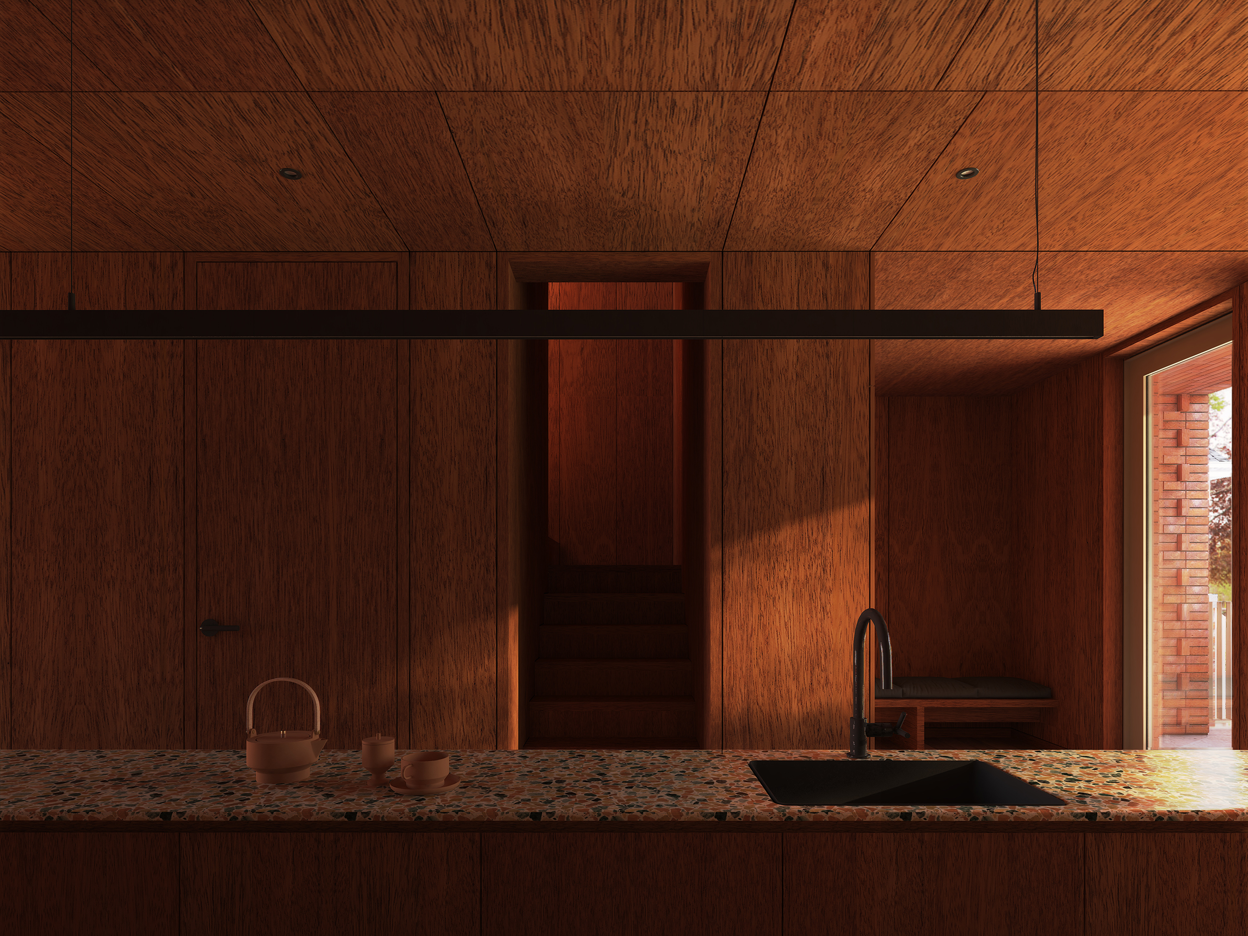 Kitchen space with view to entrance and staircase threshold, with terrazzo countertops and wood wall cladding
