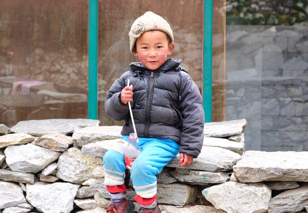 Sherpa child drinking a Coca-Cola