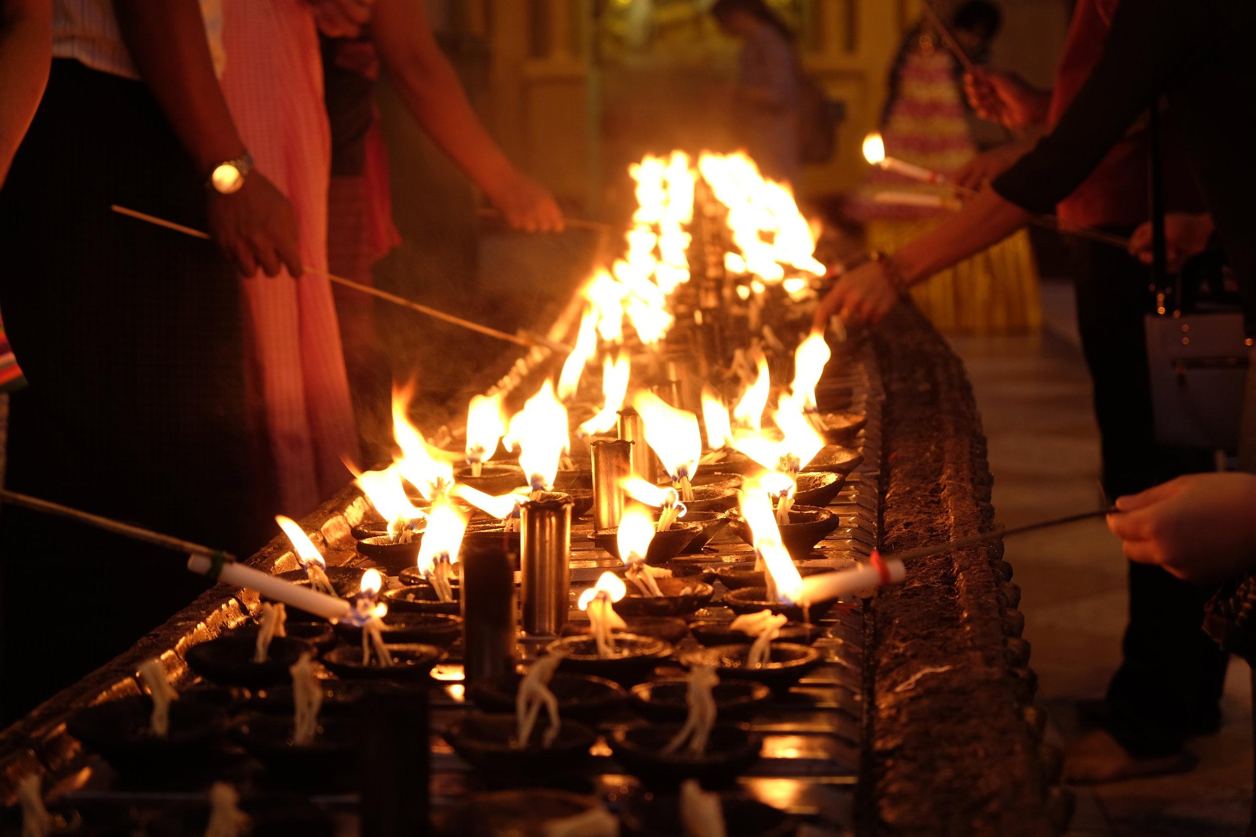Faithful lighting votives after sunset