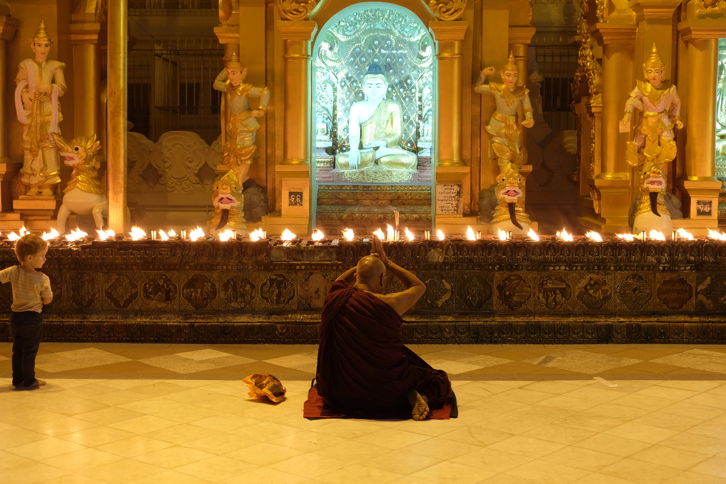 A child looks on as a monk meditates