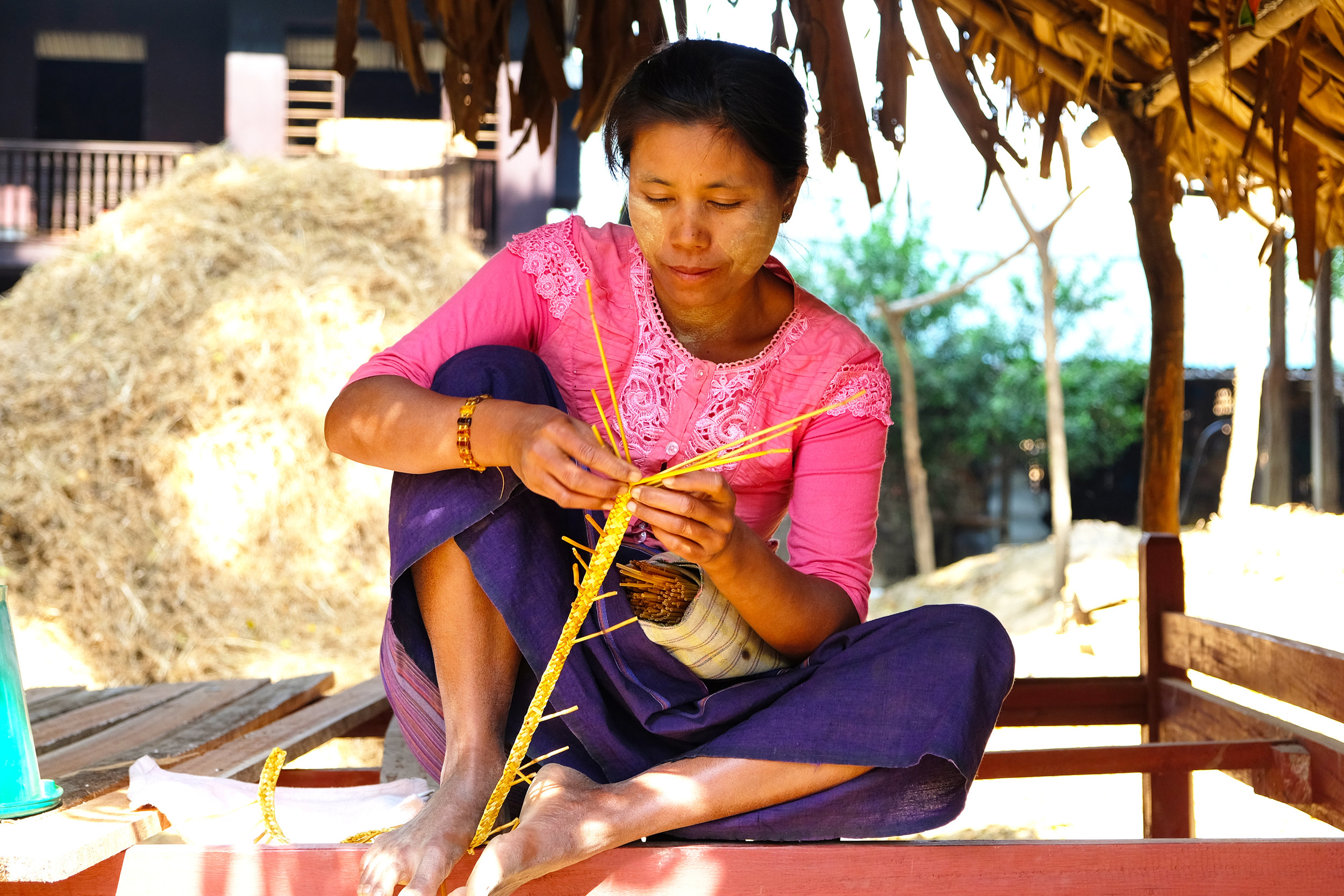 Woman weaving straw for a hat