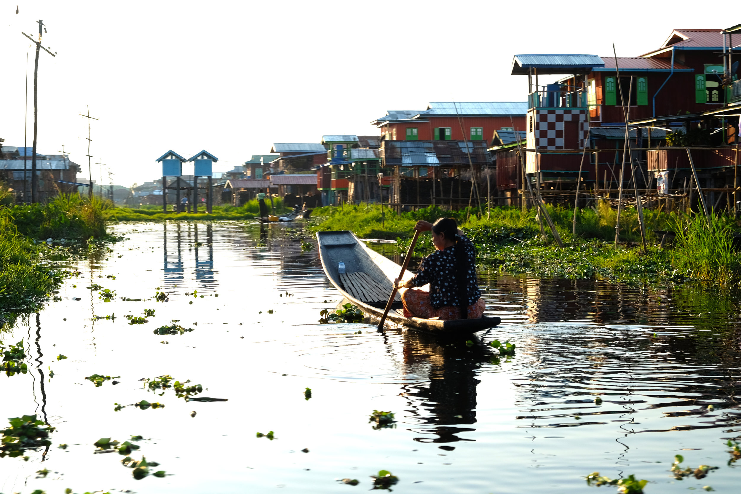 Woman rowing home in the evening on Inle Lake