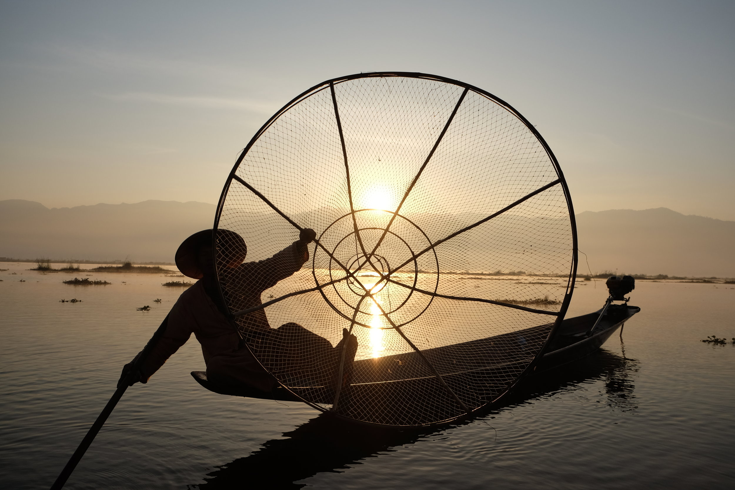 Inle Lake fisherman holding his net up to the camera at sunrise