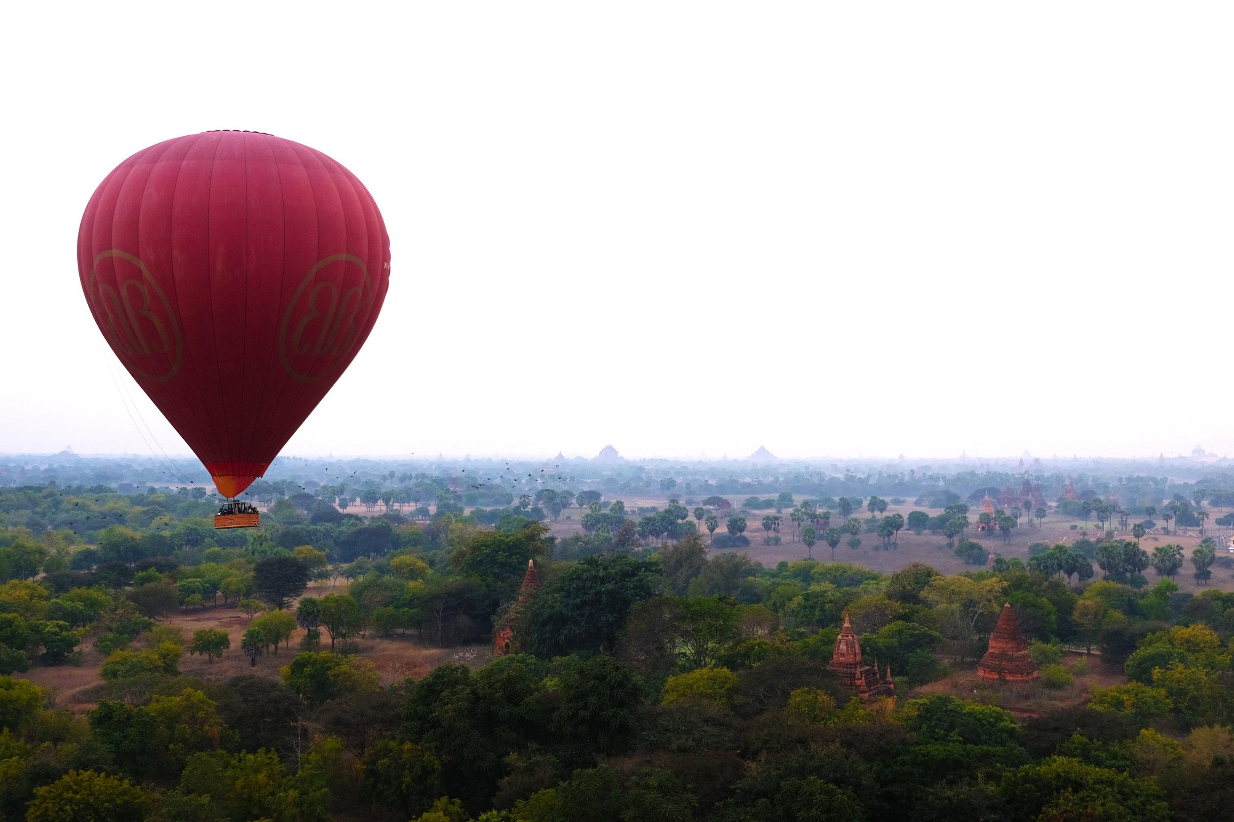 Hot air balloon passes over buddhist ruins, Bagan