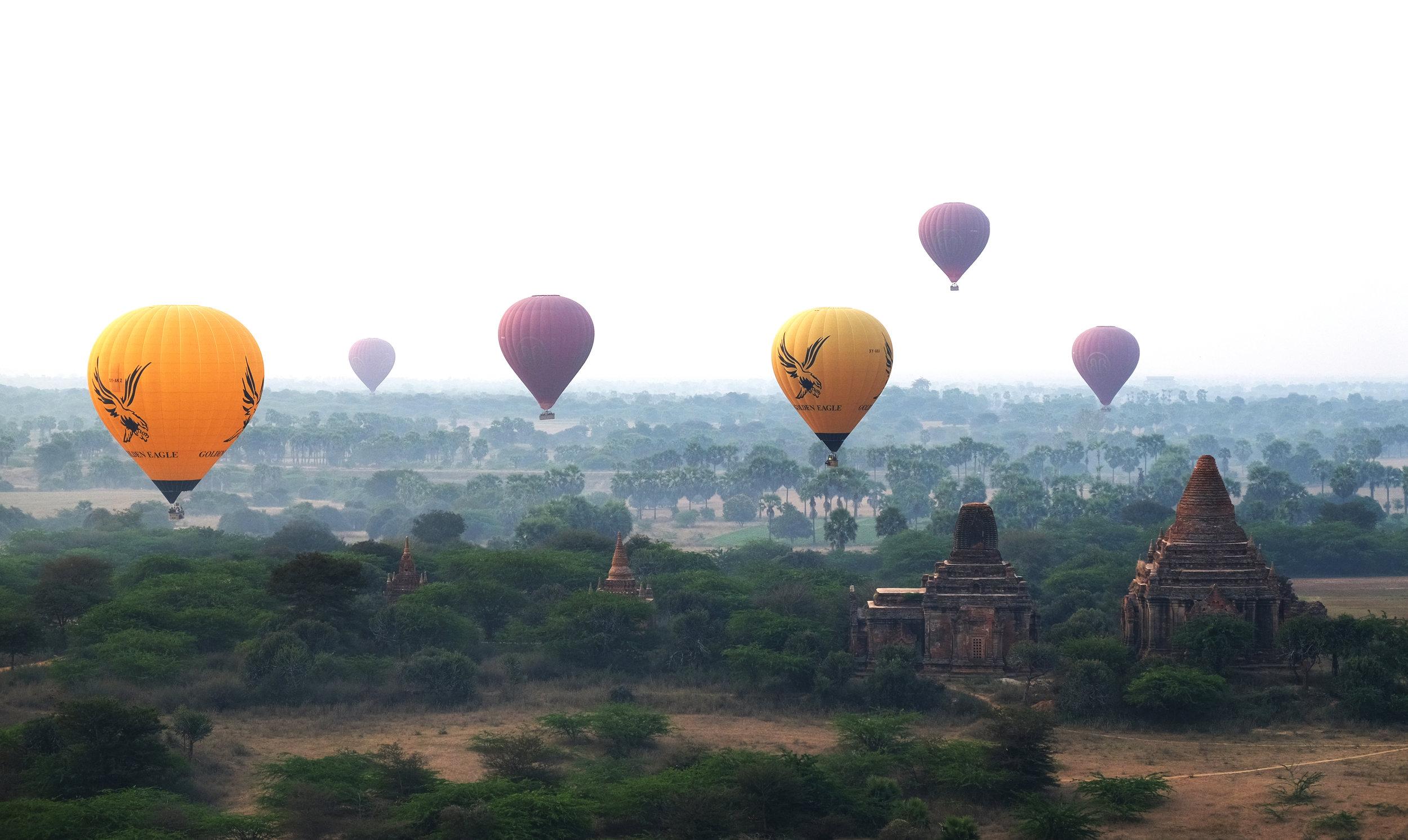 Hot air balloons passing over ruins at Bagan