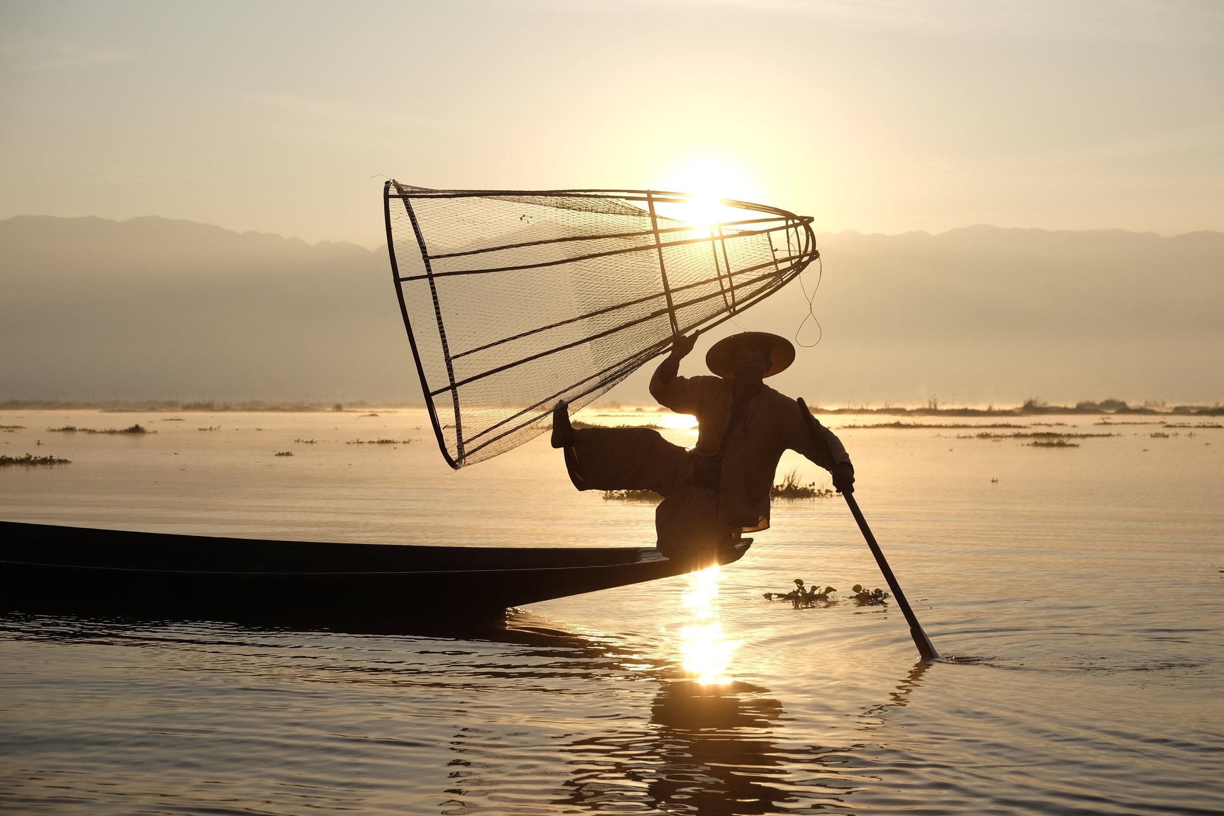 Inle Lake fisherman lifting his net at sunrise