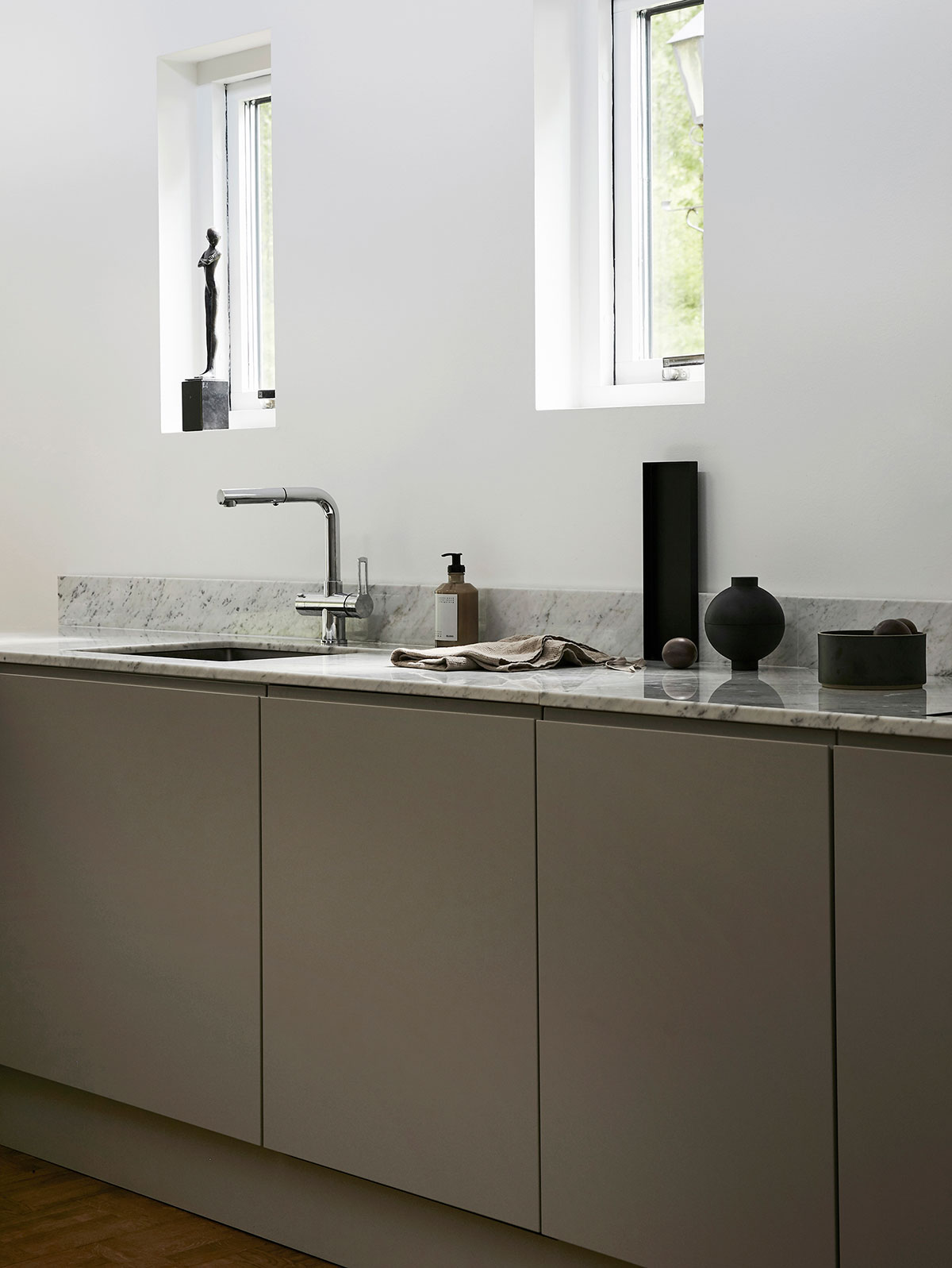 Minimalist grey kitchen in modern Scandinavian design with marble countertop