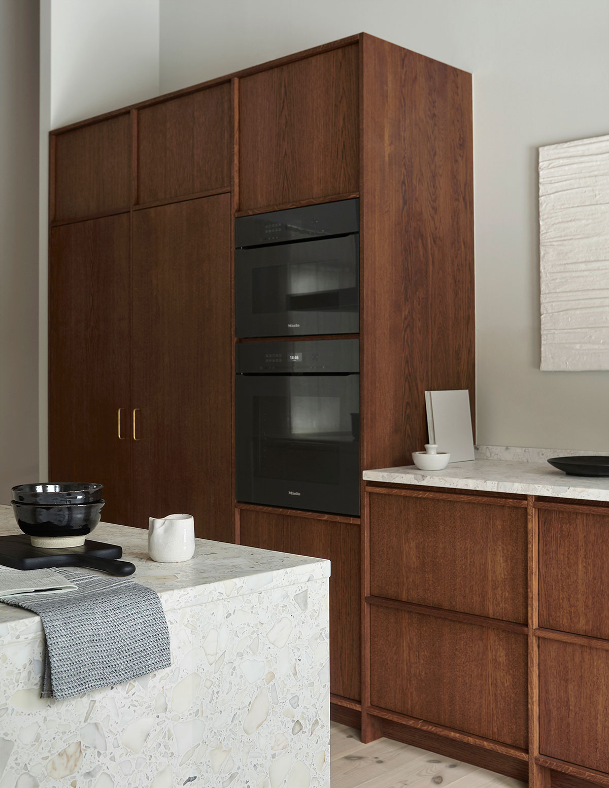 Minimalist, modern in frame oak kitchen with terrazzo countertop and Miele appliances