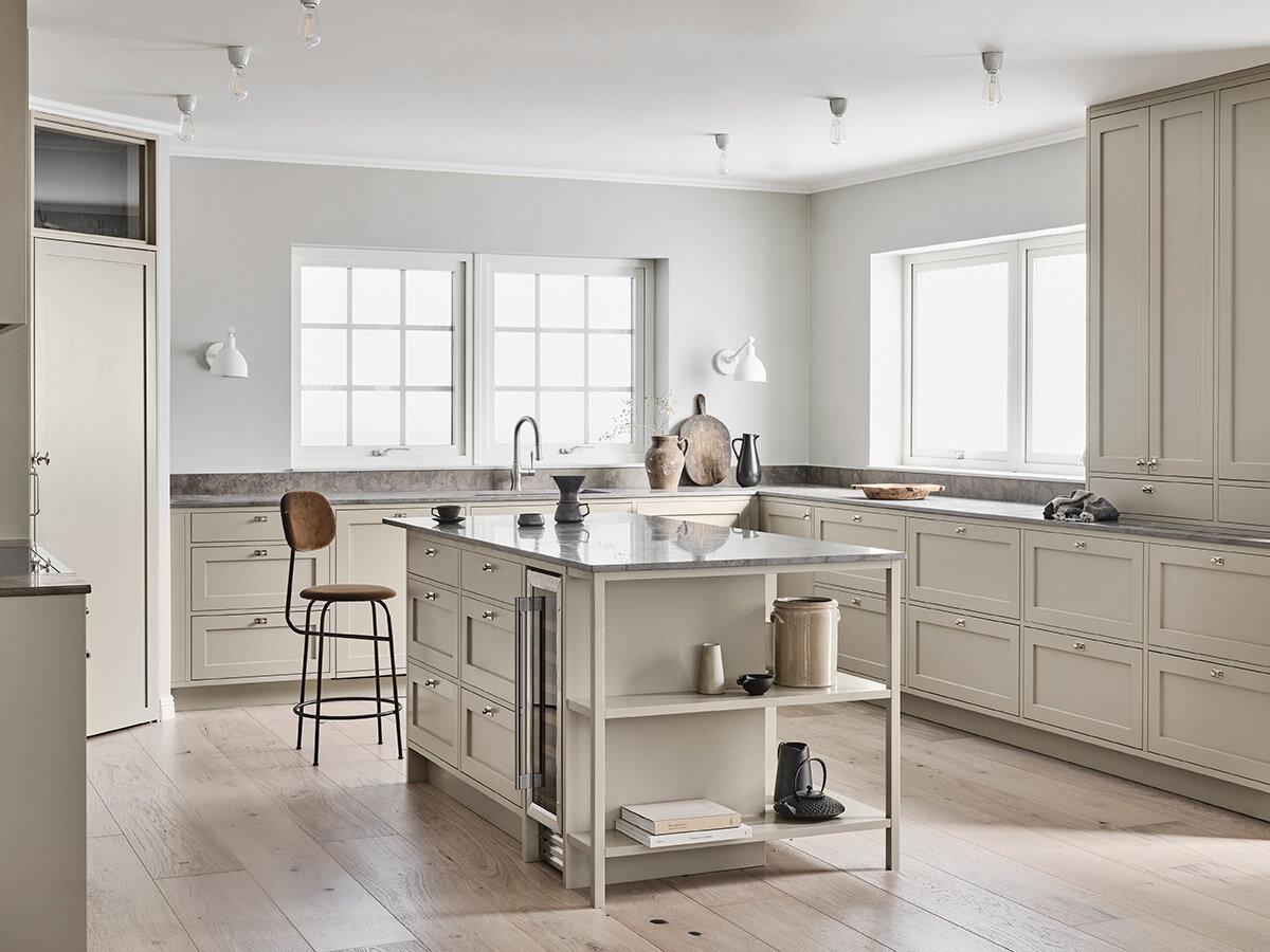 En platsbyggd köksö, ton i ton med öppen förvaring och inbyggd vinkyl. Vackert plankgolv och så fina designval i huset.
