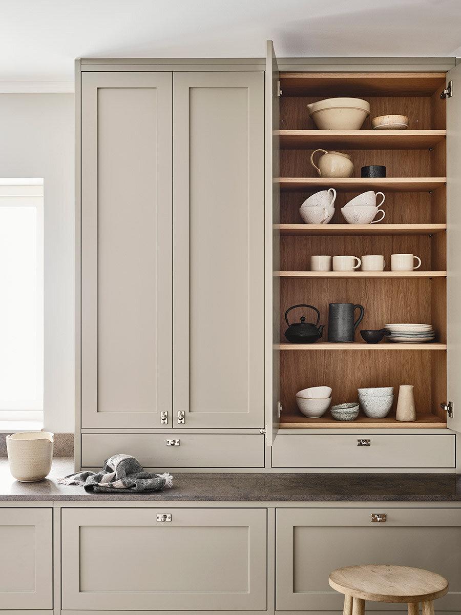 Bakom kökets dörrar gömmer sig platsbyggda skåp och lådor i ljus ek. Knopparna i silver ger en avskalad men fortfarande klassisk känsla.