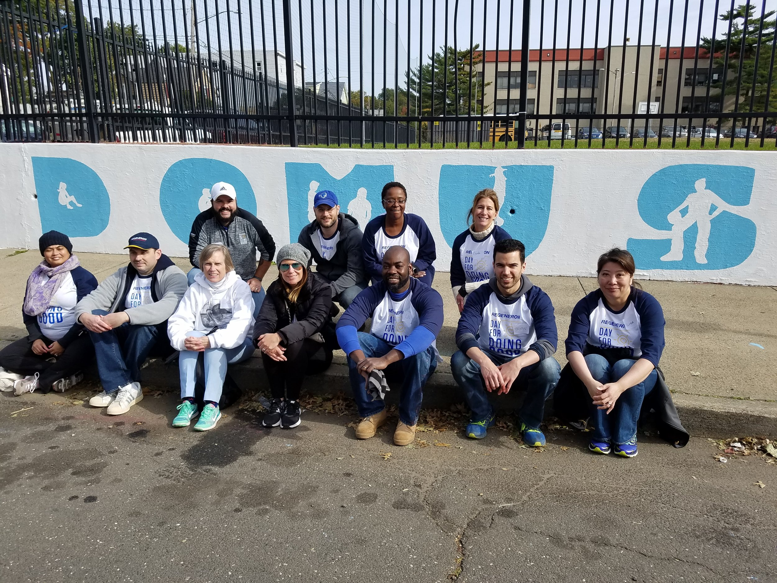 Talented Regeneron team posing for a picture after painting the new Domus logo.