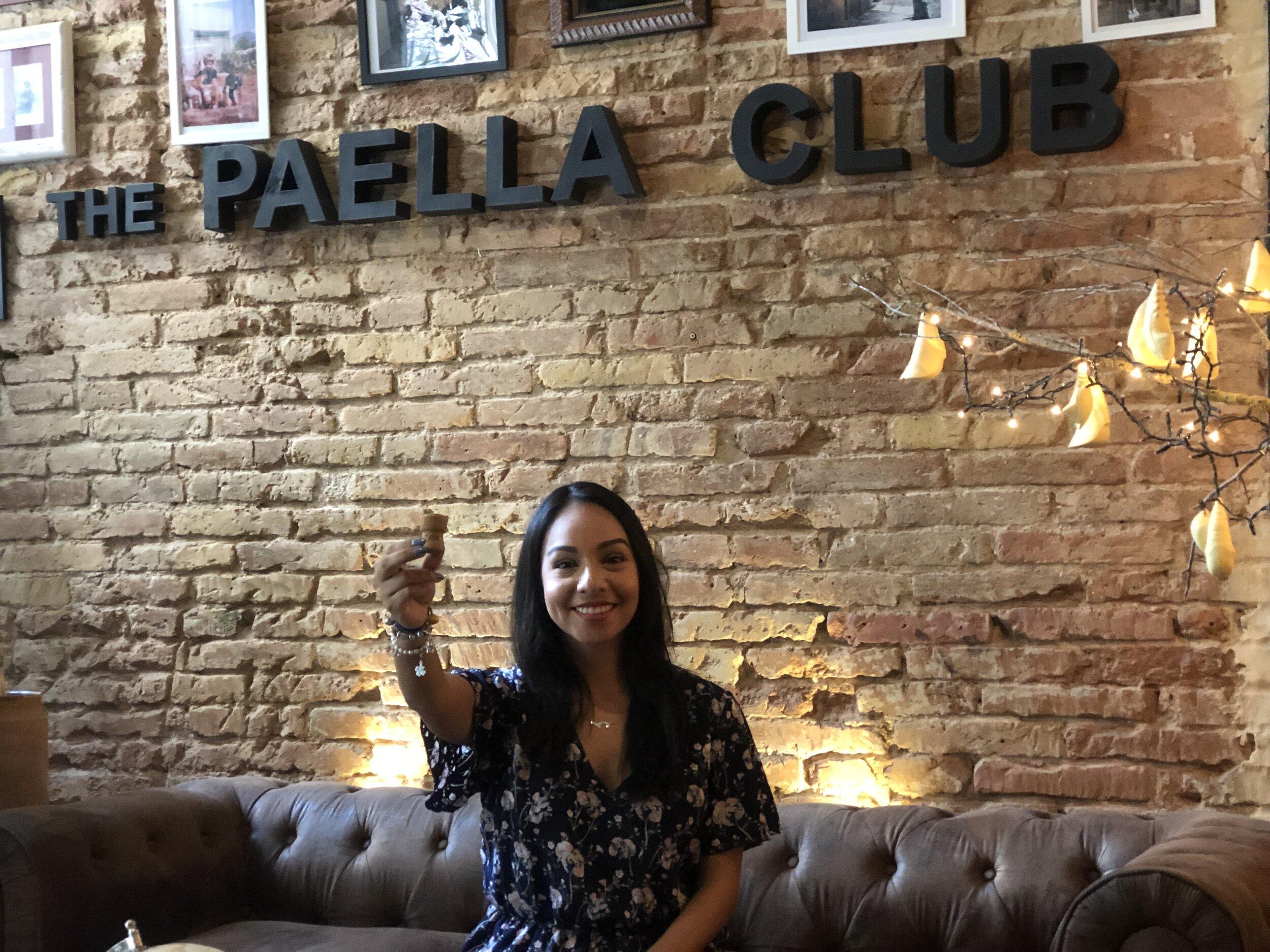 Marina muestra orgullosamente un corcho, una pieza clave para el proyecto Aflote, frente al logo de The Paella Club, en la entrada del restaurante, al principio de la entrevista.
