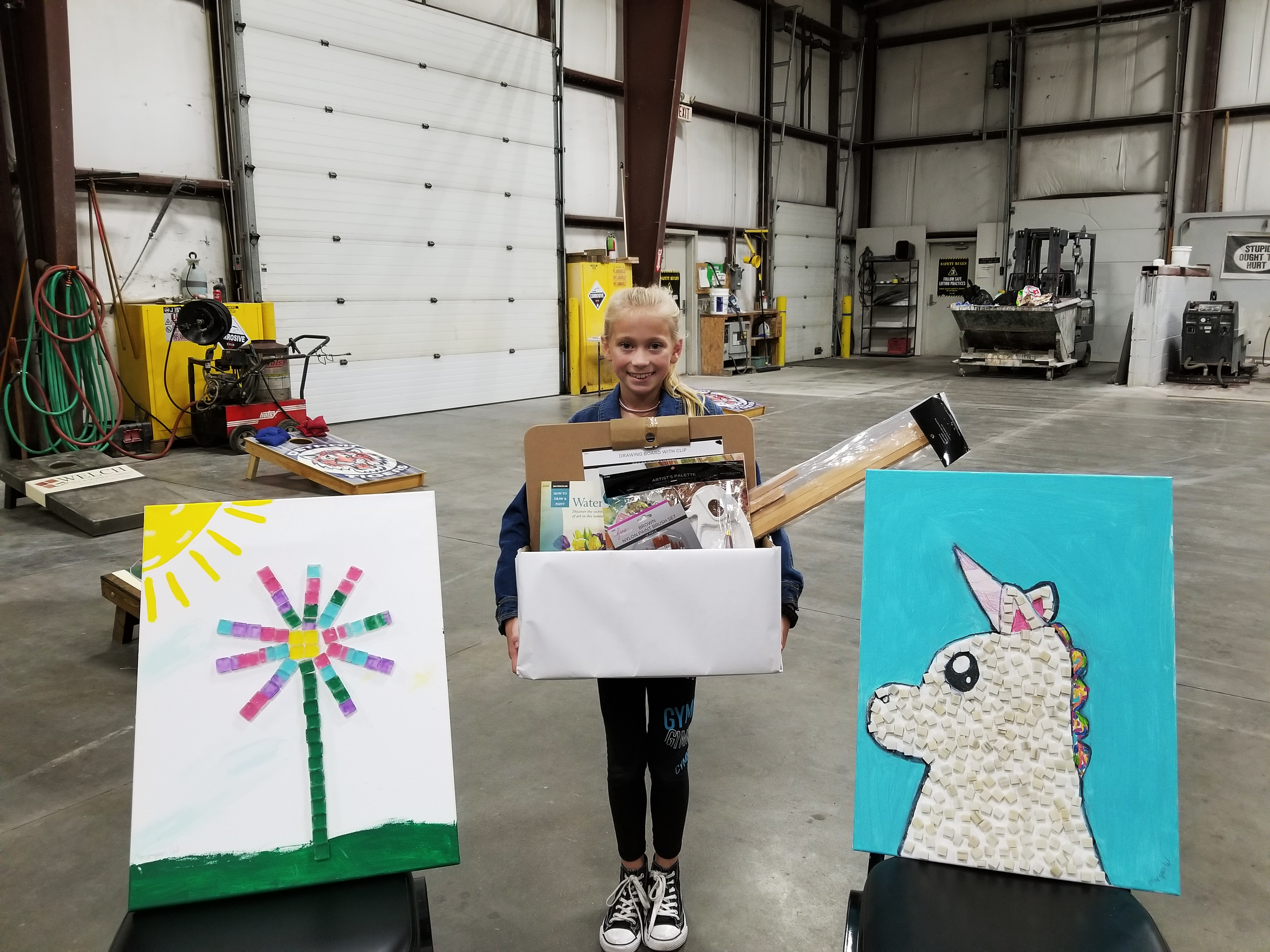 The winner of our art contest with her submissions and her prize
