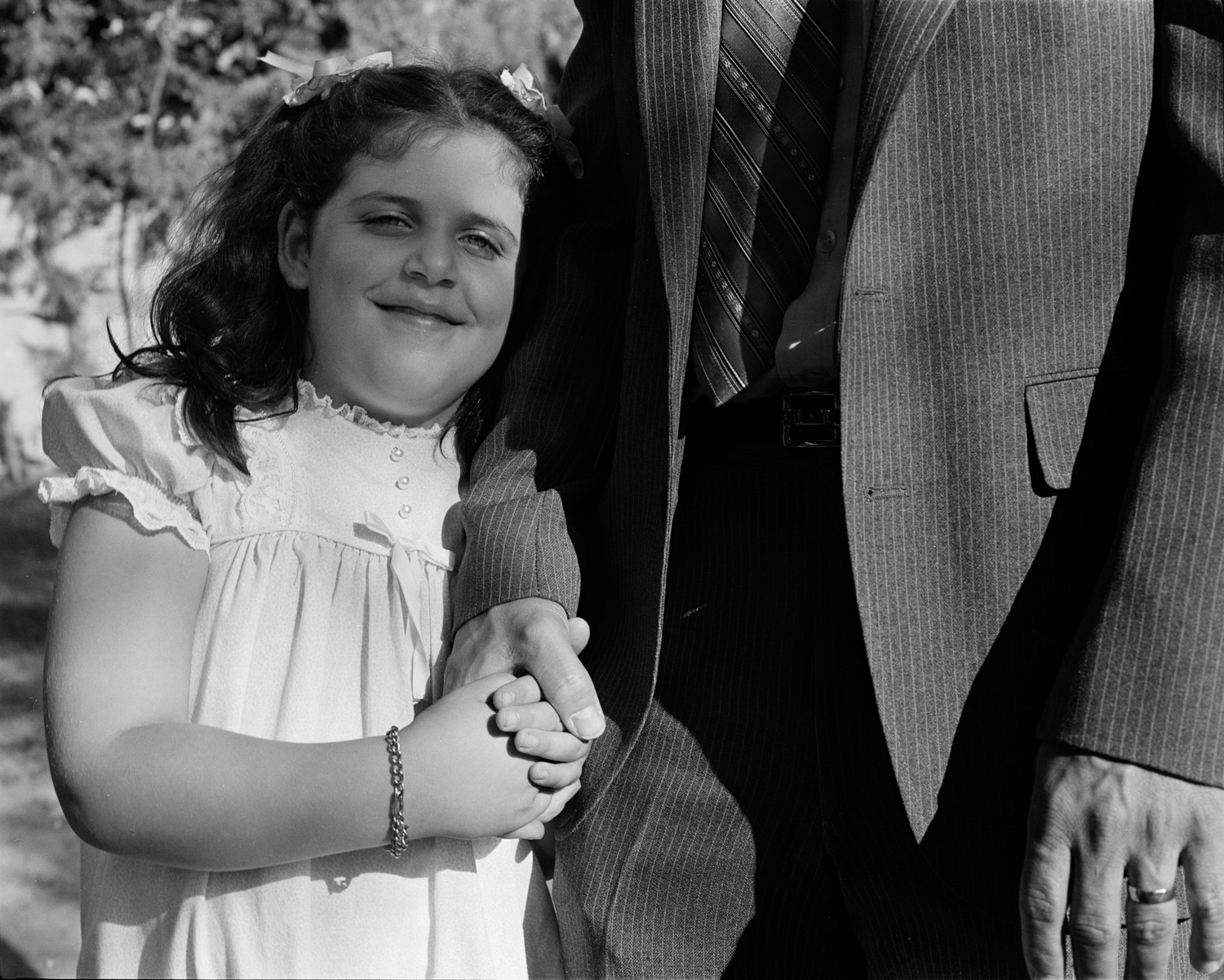 Girl holding her father's hand, Los Angeles, CA, 1984