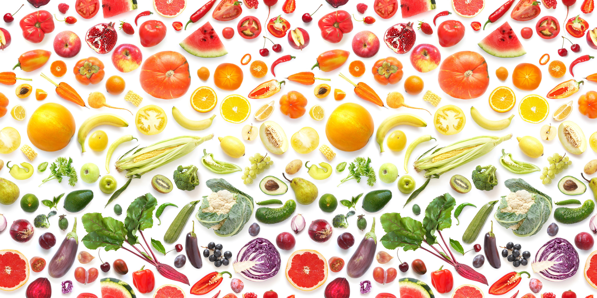 Photo of all different color veggies arranged in a rainbow.