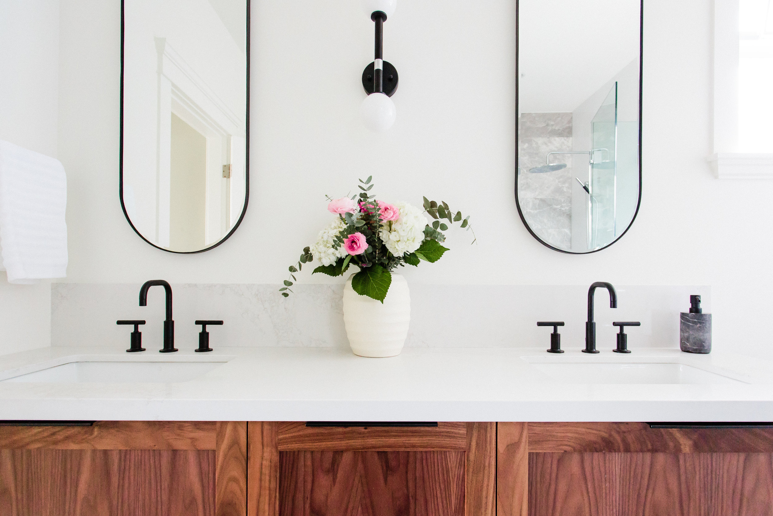 Stunning marble meets vibrant walnut in the master bathroom while thick quartz countertops cap the kitchen cabinets.