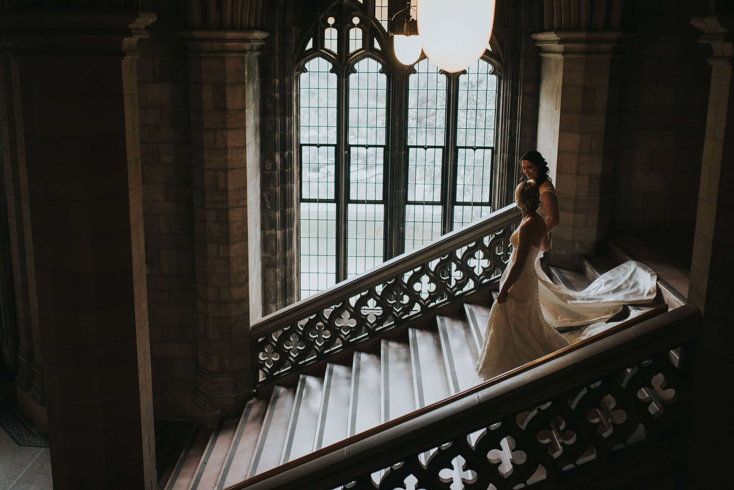 brides-walking-down-staircase-knox-college-toronto-same-sex-wedding-willow-and-birch-photography-documentary-wedding-photographers.jpg