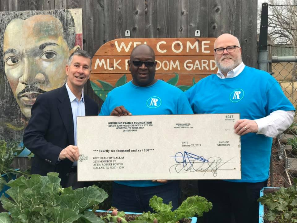 Seedling Farm Master Gardener and Manager, Tyrone Day (middle) accepts a check from a representative of the Interlinc Family Foundation. Far right is Dr. Owen Lynch, founding member of the Restorative Farms team.