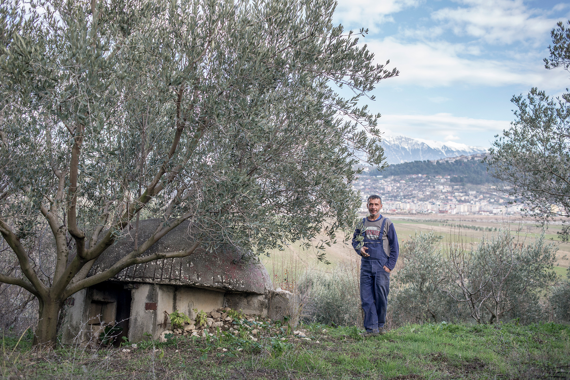 The owner of the orchard stands near the bunker, Ura Vajgurore, Albania