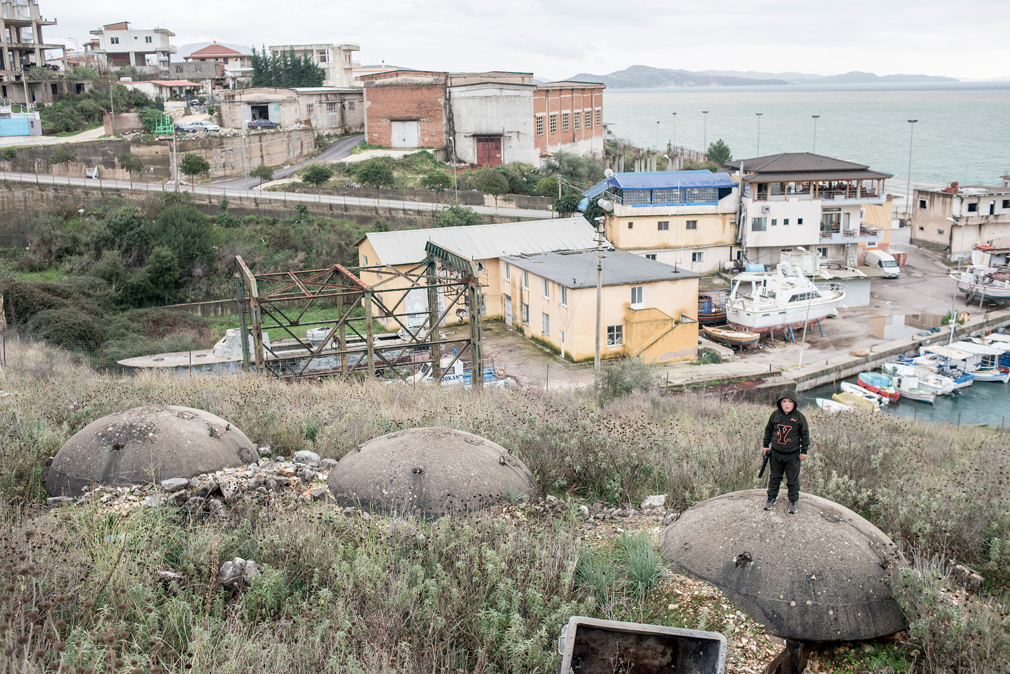 A boy with a toy gun stands on a bunker near the port, Saranda, Albania