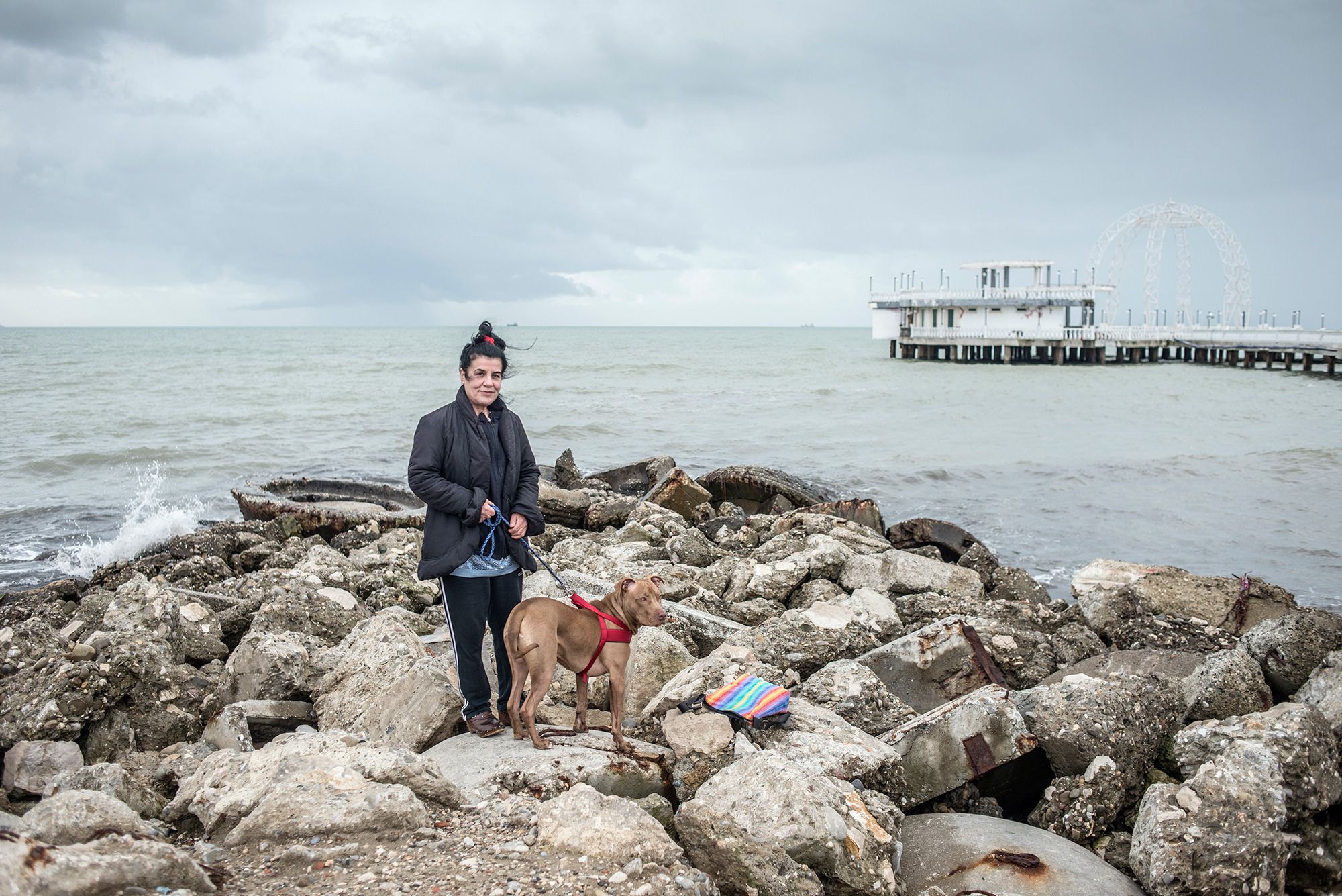 A woman walks a dog on a background of abandoned bunkers, Durres, Albania