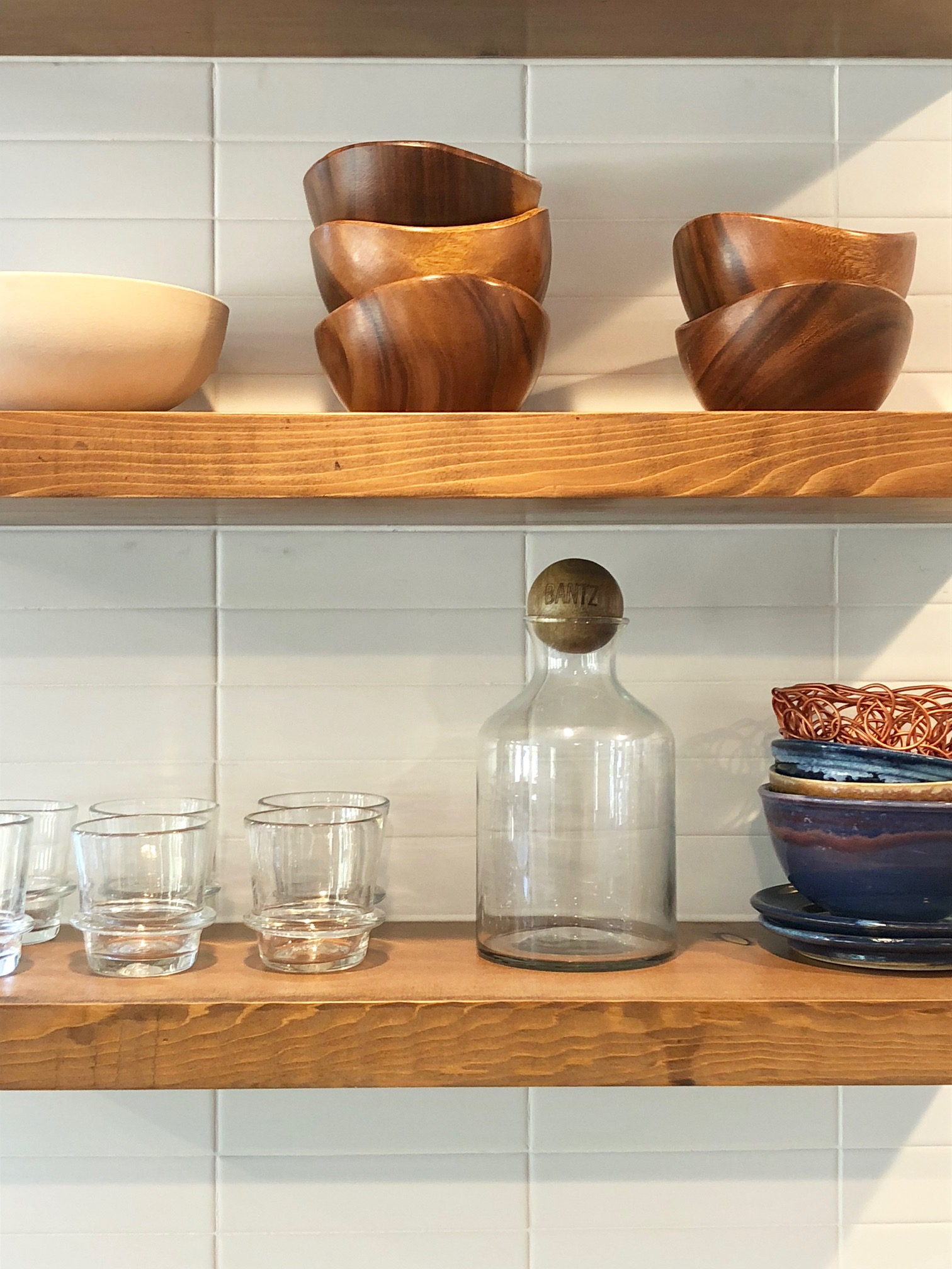DITCH THOSE UPPERS - A lot of time and energy during a remodel is put towards opening up a kitchen and making a living space feel more open and connected. A simple way do achieve this feel, if you have a limited budget, or even if you don't, is to ditch the existing upper cabinets. There are a number of reasons why I love this trend. First off, open shelving emphasizes your backsplash and allows you to take it counter-to-ceiling. Second, it can bring in a more textured material like wood to expand your color palette. Third and most importantly, it forces you to take a look at your dishware and decide what you love and want to display. Surprisingly you'll start using things you might not have, more often because they're so easily accessible.California Sawdust is a local company that fabricates custom wood furniture and home decor with a clean rustic sensibility.