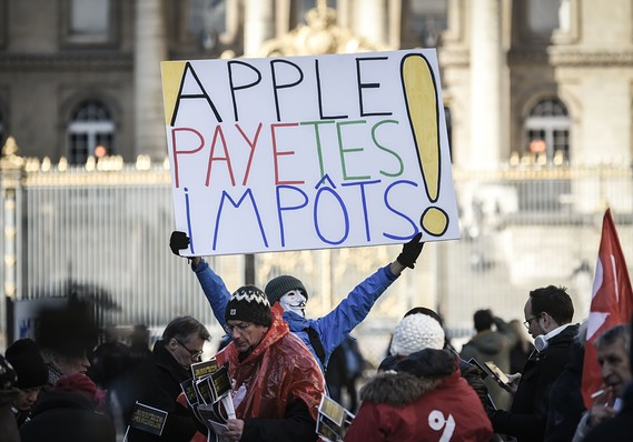 "STEPHANE DE SAKUTIN/AFP/Getty Images  French activist Jean-Baptiste Redde holds a placard reading ""Apple pay your taxes"" at a protest in Paris in February 2018"