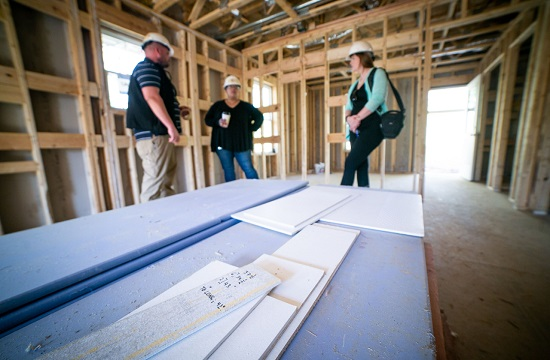 Pictured: Kelli Palmer, CFA Institute Director of Corporate Citizenship, during a walk-through at the Harmony Ridge neighborhood. CFA Institute is partnering with Habitat for Humanity on a pilot Carbon Offset Project in Harmony Ridge to help the non-profit maximize its use of energy-use reduction techniques and materials in the homes' construction.
