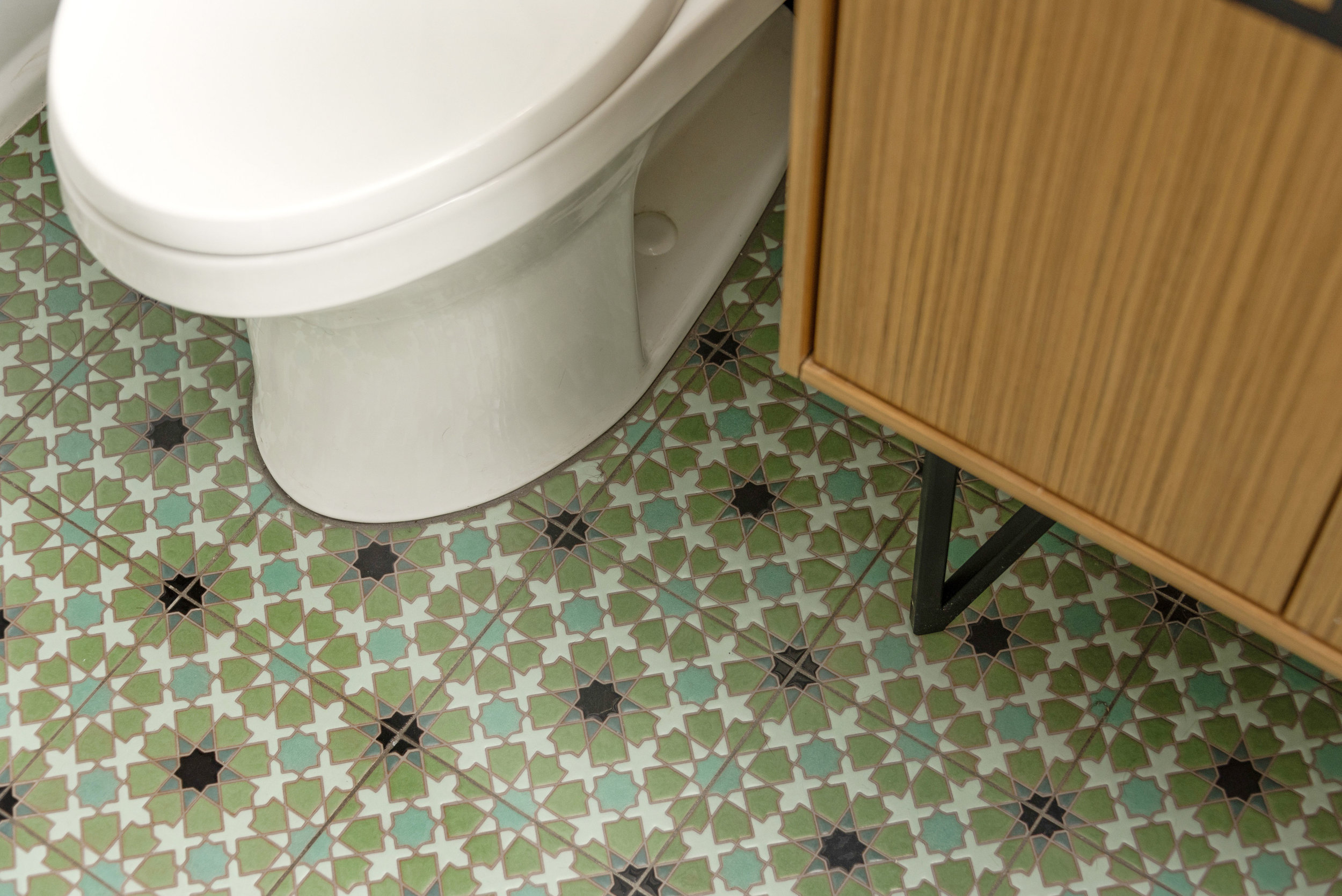 The  Kohler Jute vanity  in Corduroy Teak features classic Mid-Century hairpin legs. This is a great way to showcase the beautiful pattern  Fireclay tile floor .