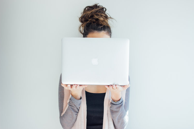 Women holding laptop with top knot